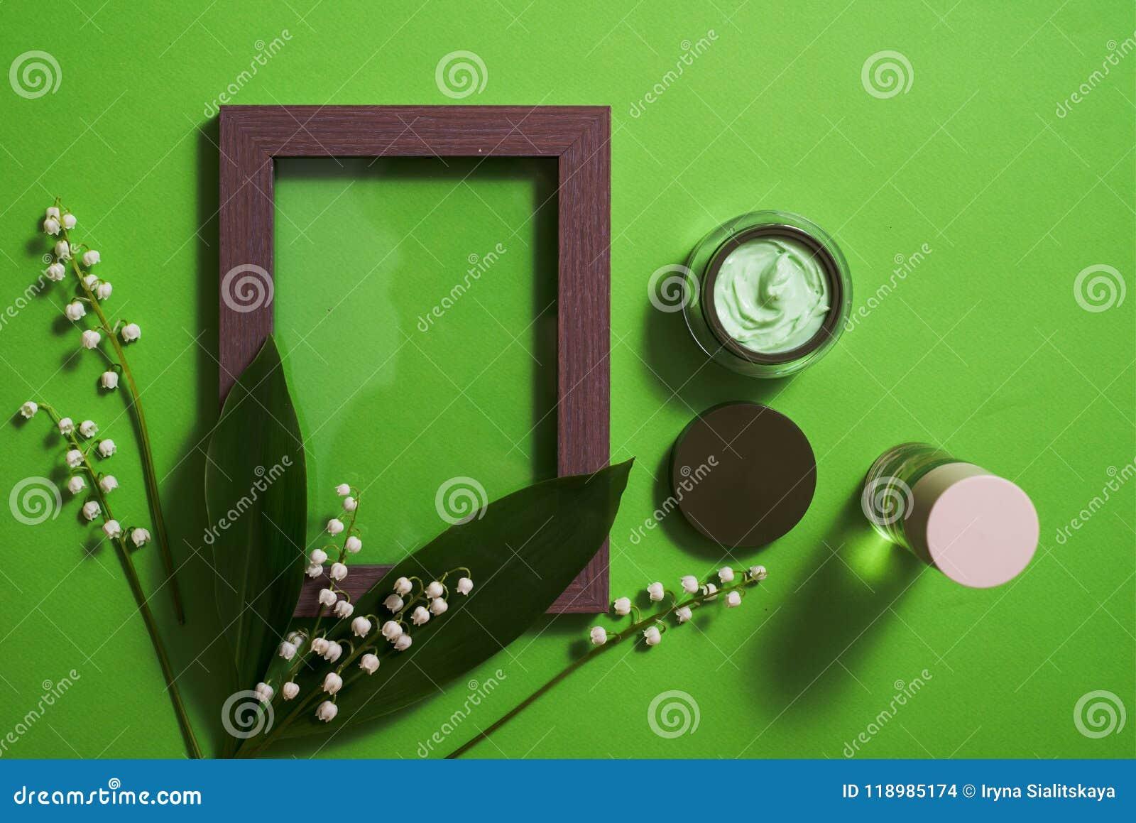 Fleurs cosmétiques de crème et du muguet sur un fond vert