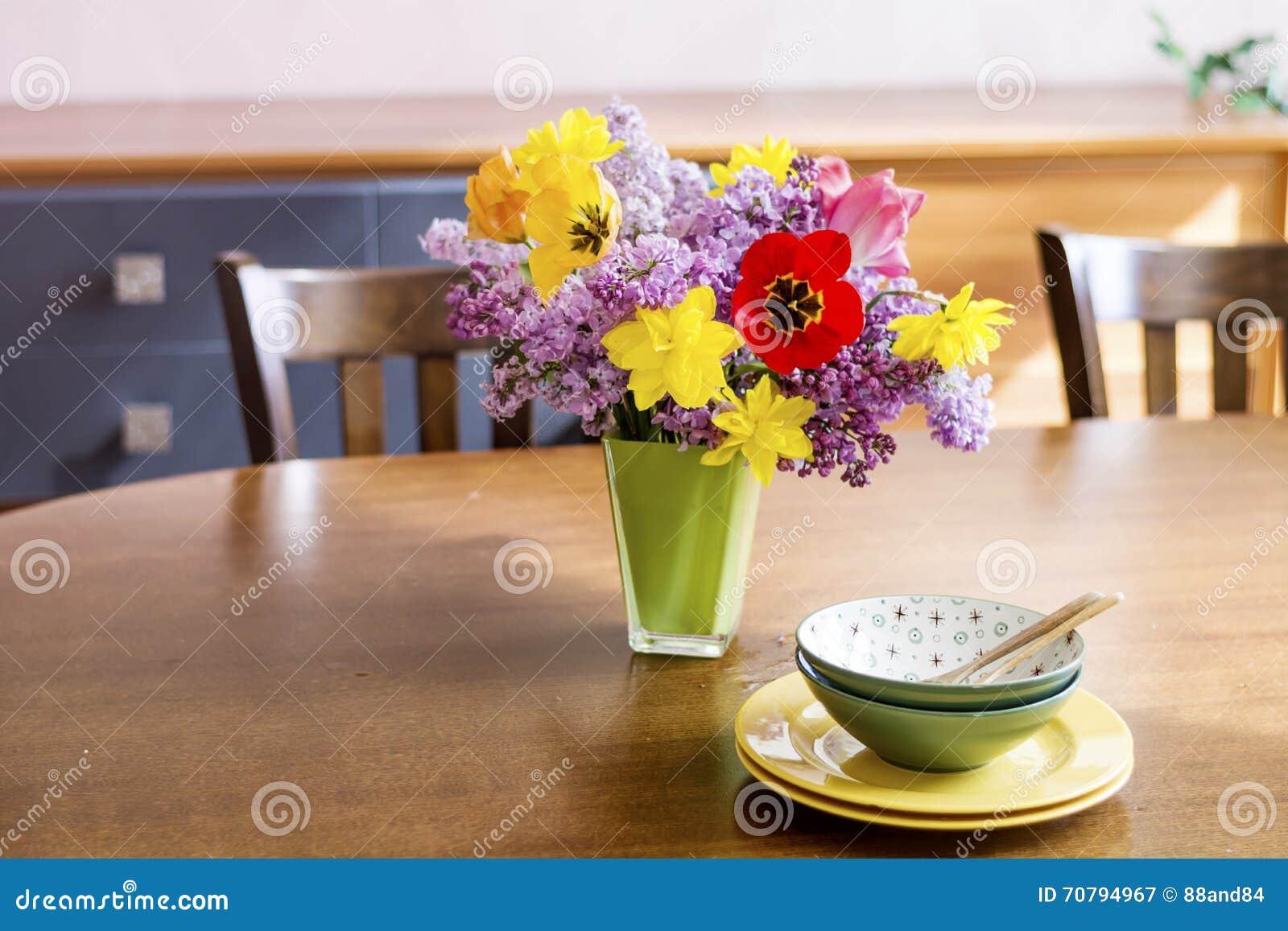 fleurs de tulipes de narcisse et de lilas dans un vase en verre vert sur une table en bois. Black Bedroom Furniture Sets. Home Design Ideas