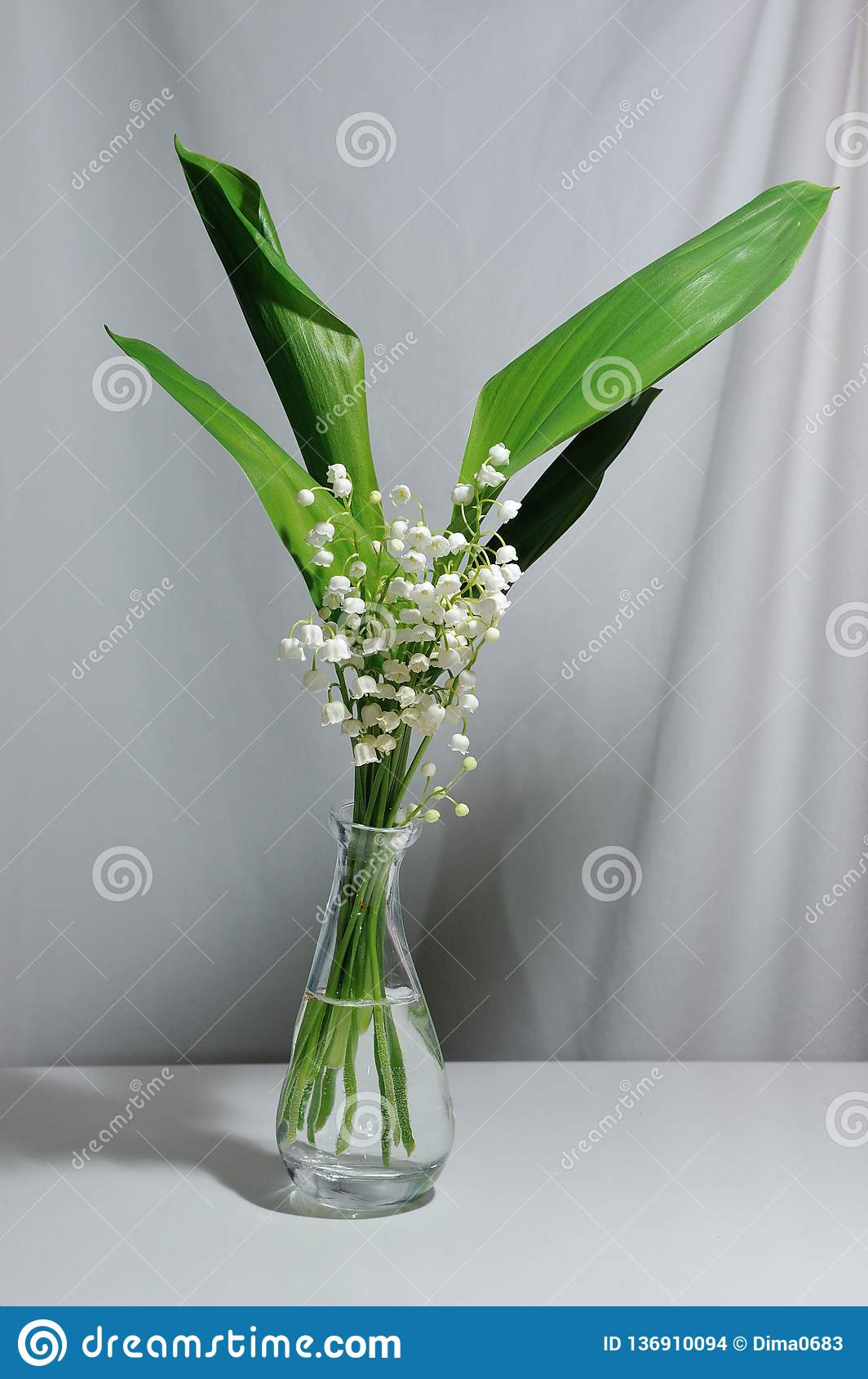Fleurs du muguet dans un vase transparent