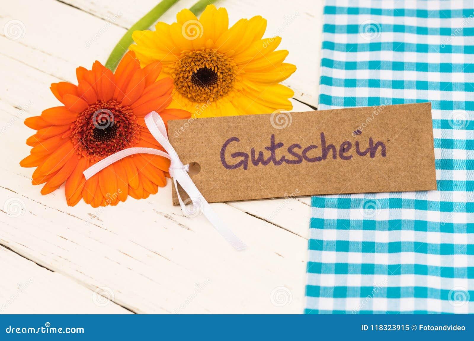 Fleurs et carte cadeaux avec le mot allemand, le Gutschein, le bon de moyens ou le bon pour le jour ou l anniversaire du ` s de p