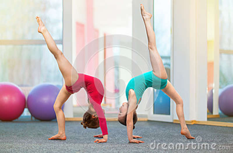 Flexible kids gymnasts doing acrobatic exercise in gym. Sport concept
