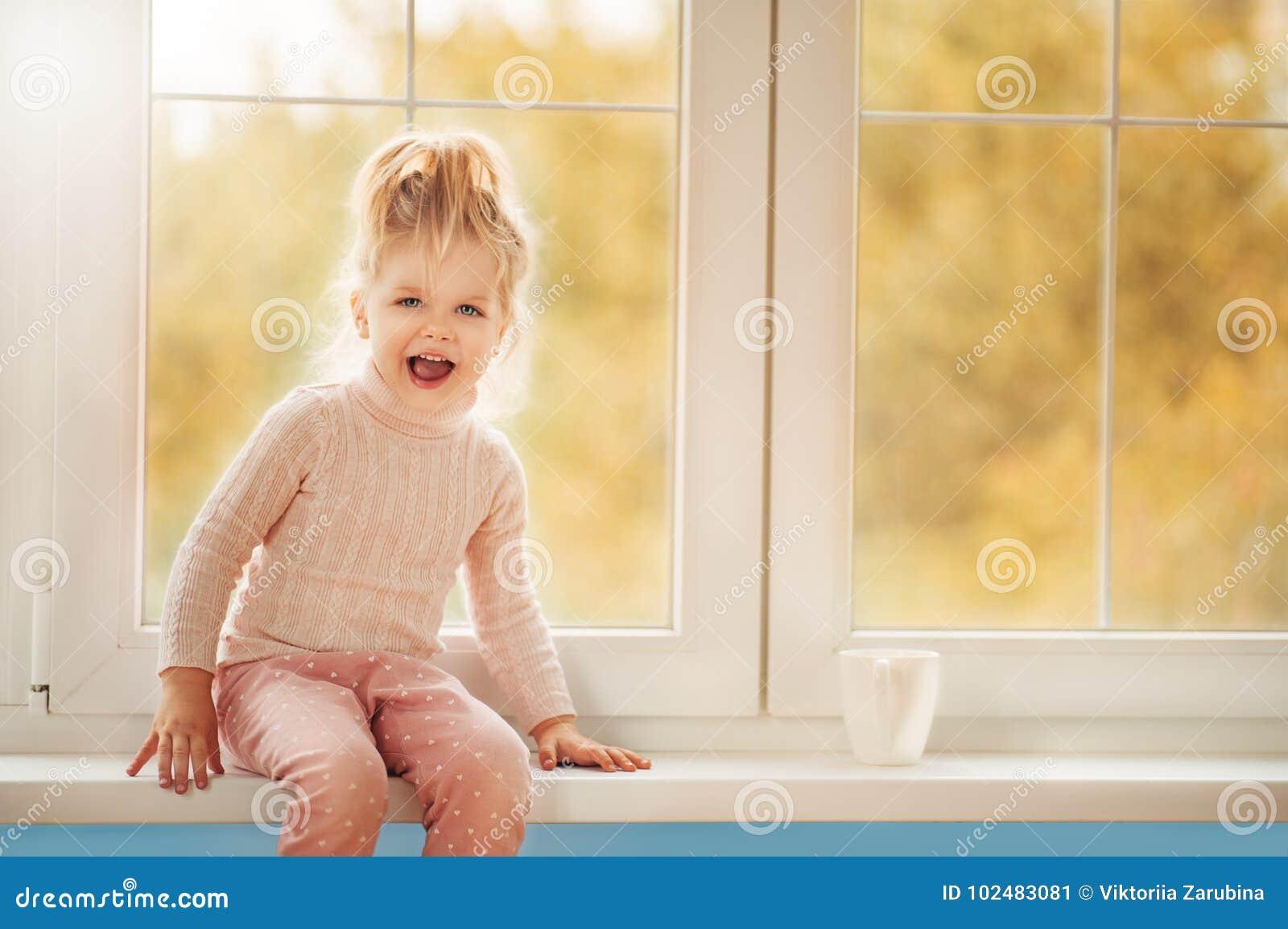 Flicka för liten unge för Ð-¡ ute i pajamasammanträde av det stora fönstret som spelar le att tycka om hem Kakaokoppanseende på f