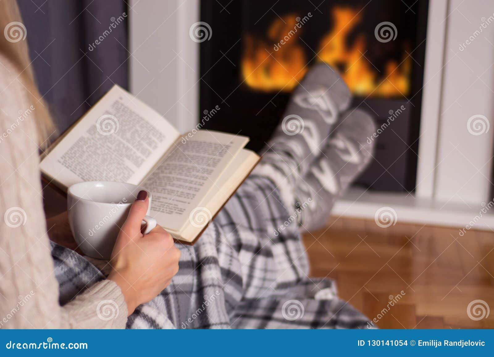 Flicka framme av läsebok- och värmefoten för spis på brand