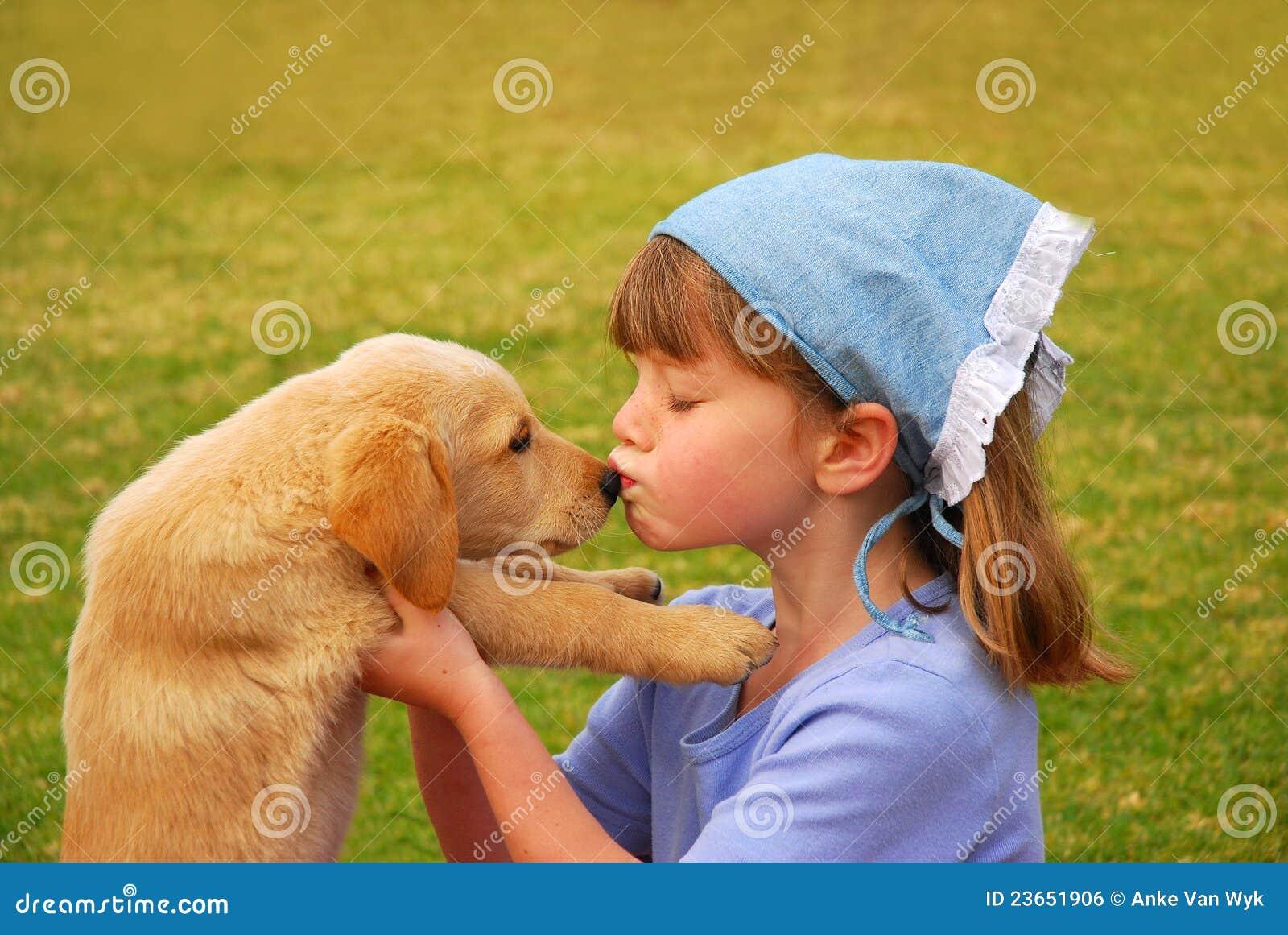 Flicka henne kyssande liten valp