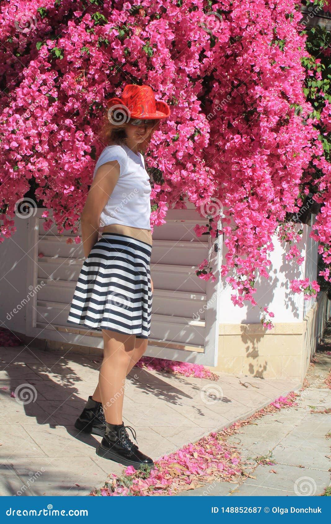 Flicka i cowboys hatt bredvid rosa blommor
