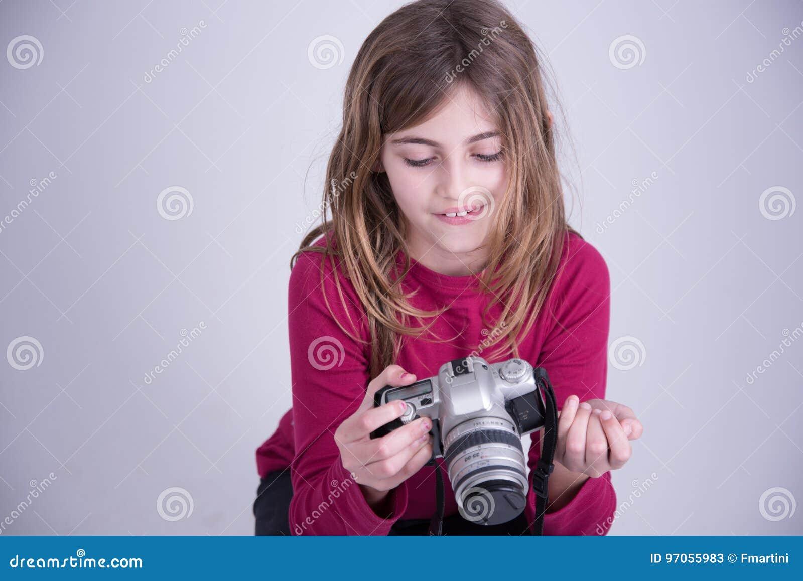 Flicka i den röda skjortan som rymmer den gamla kameran och att le