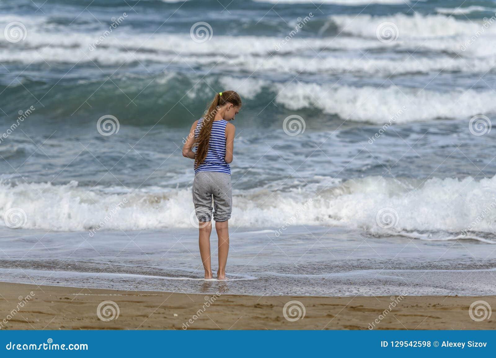 Flicka i den randiga t-skjortan som kör längs stranden