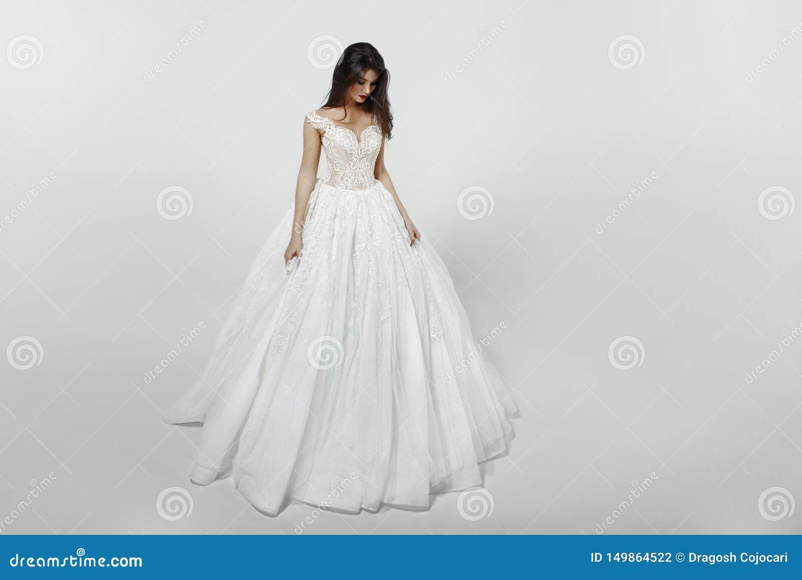 Flicka i den vita prinsessamodebröllopsklänningen som isoleras på en vit bakgrund