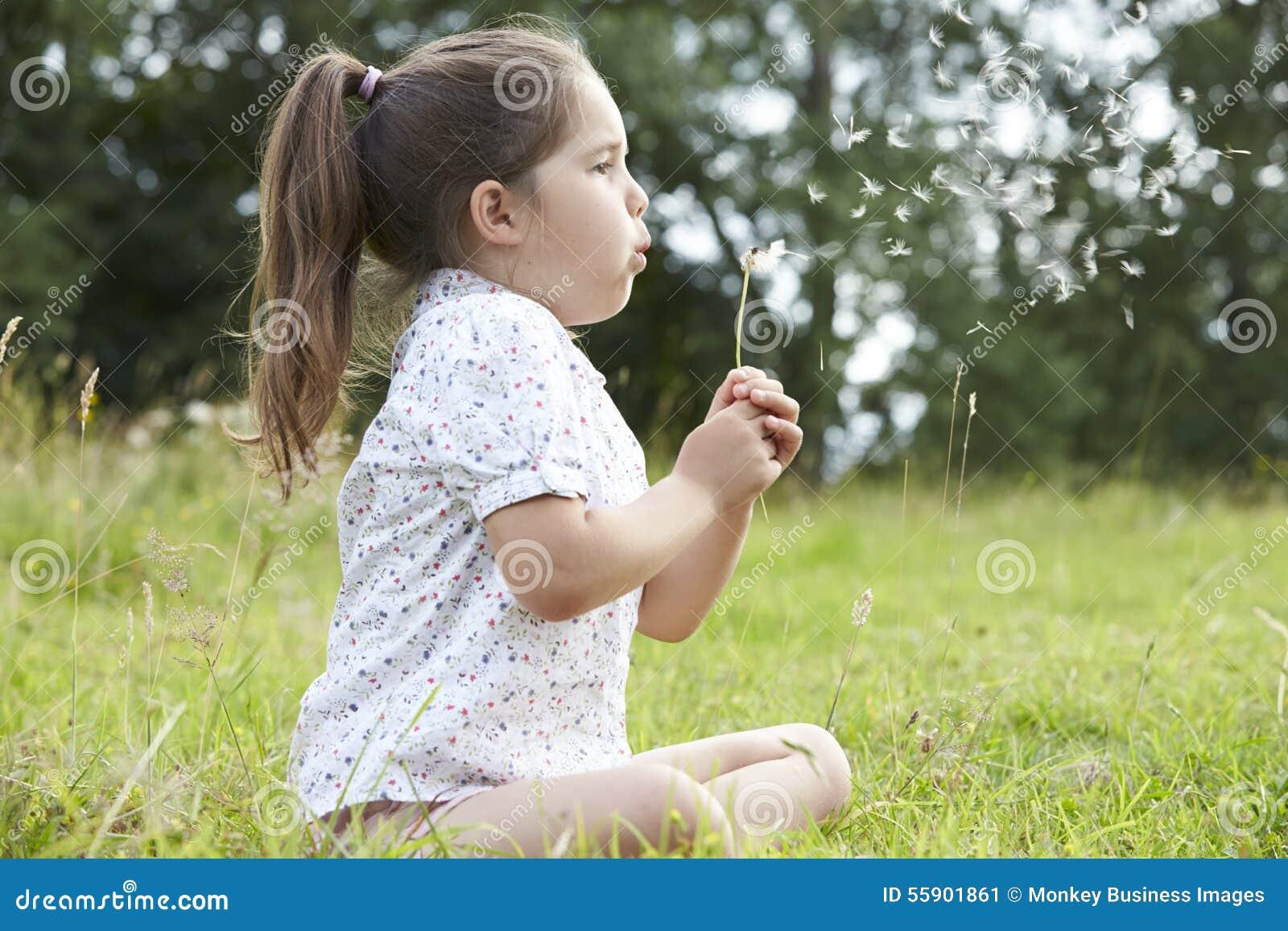 Flicka i fält som blåser frö från maskrosen