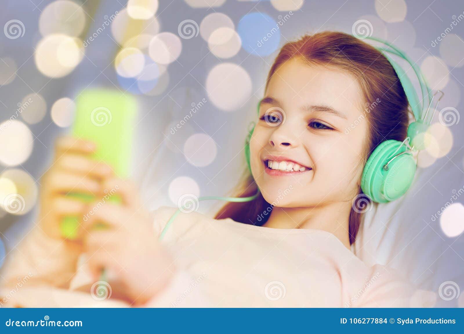 Flicka i hörlurar med smartphonen över ljus