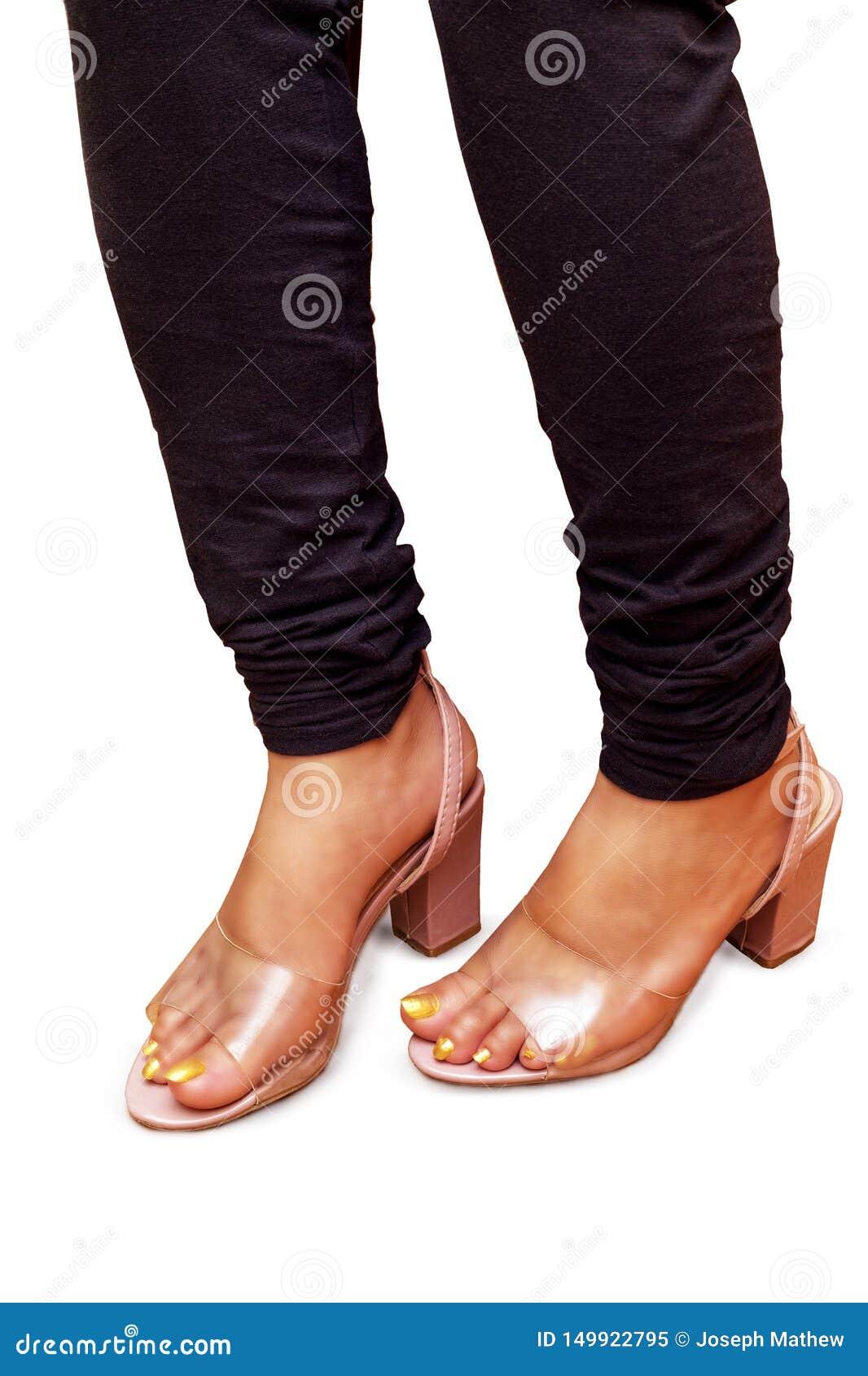 Flicka i staden som bär mörk jeans och genomskinliga rosa sandaler