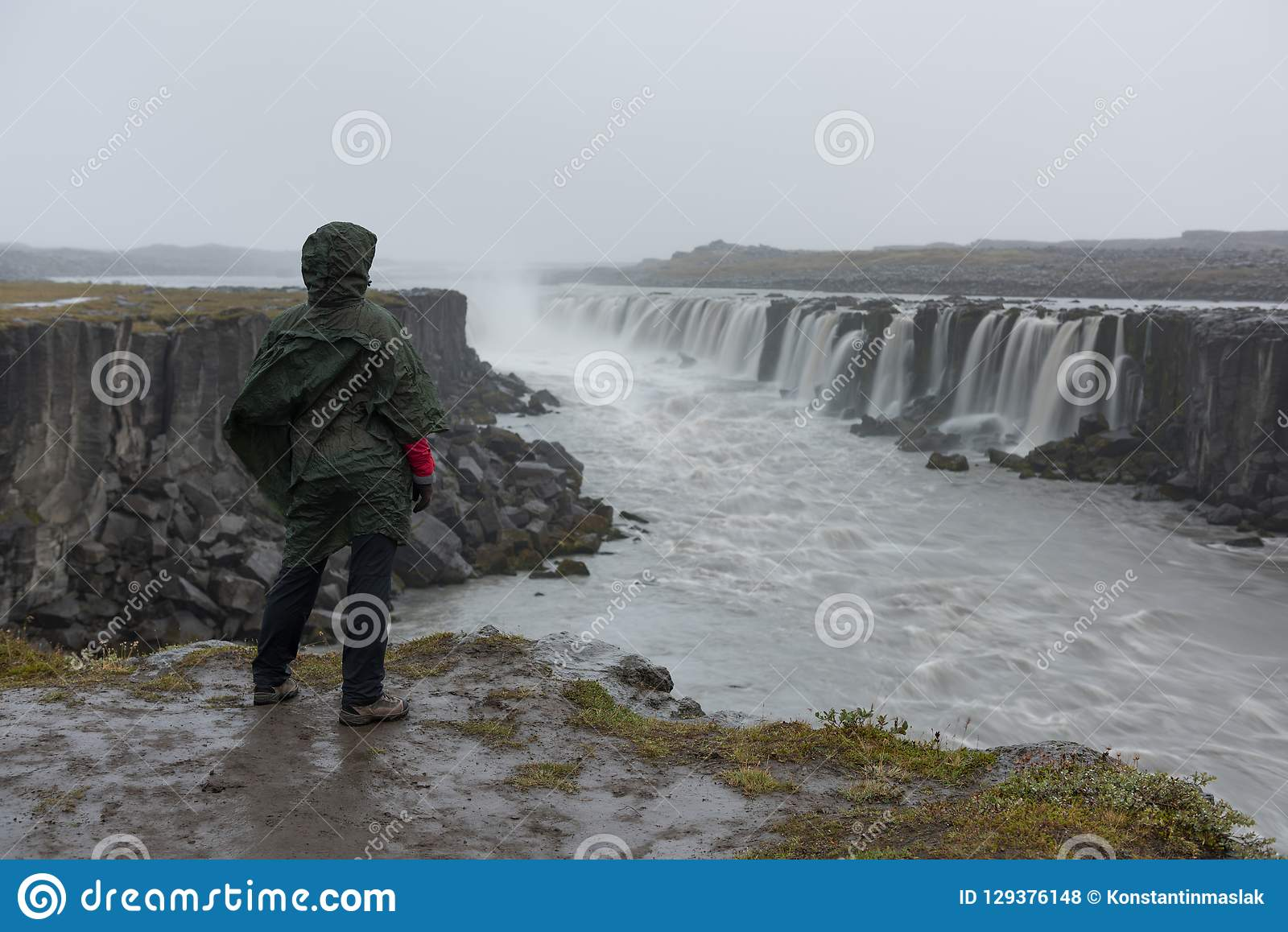 Flicka i vattentäta omslagsställningar på klippan på bakgrund av vattenfallet i Island