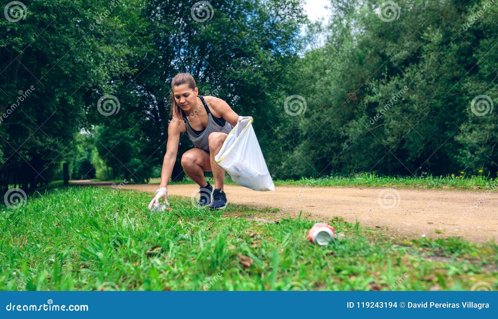 Flicka med avskrädepåsen som gör plogging