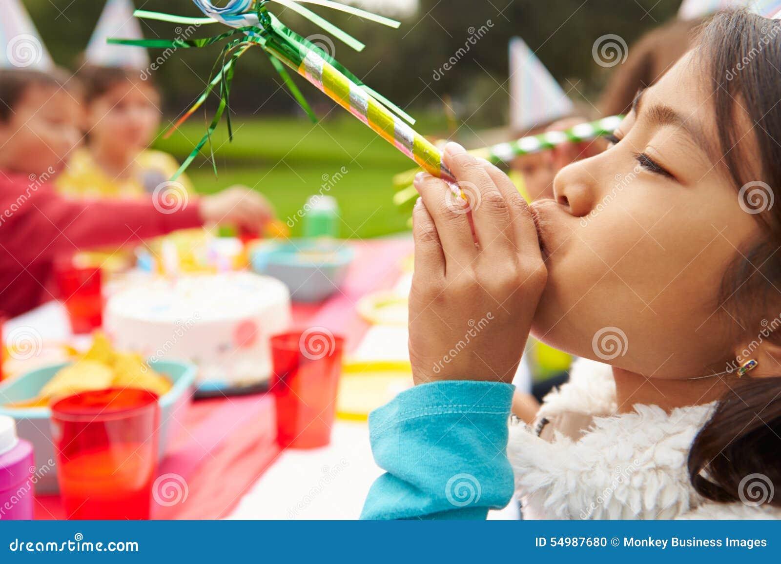 Flicka med blåsaren på det utomhus- födelsedagpartiet