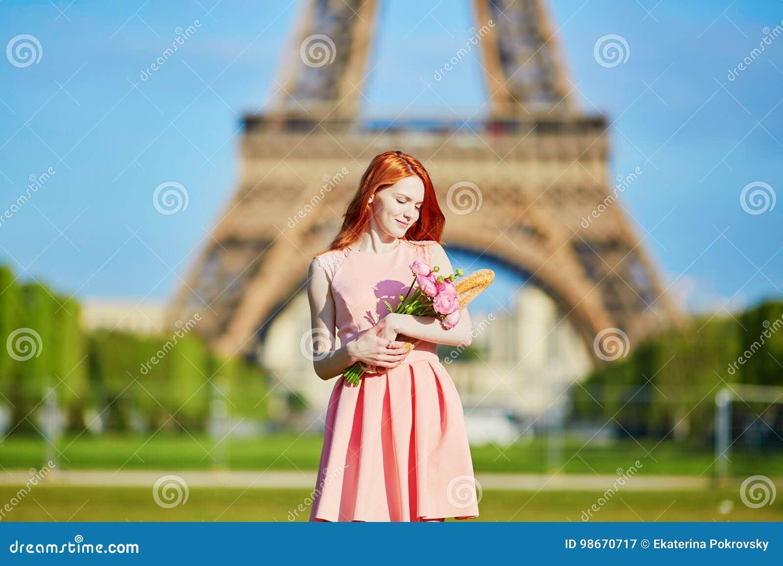 Flicka med den traditionella franskbrödbagetten och blommor framme av Eiffeltorn