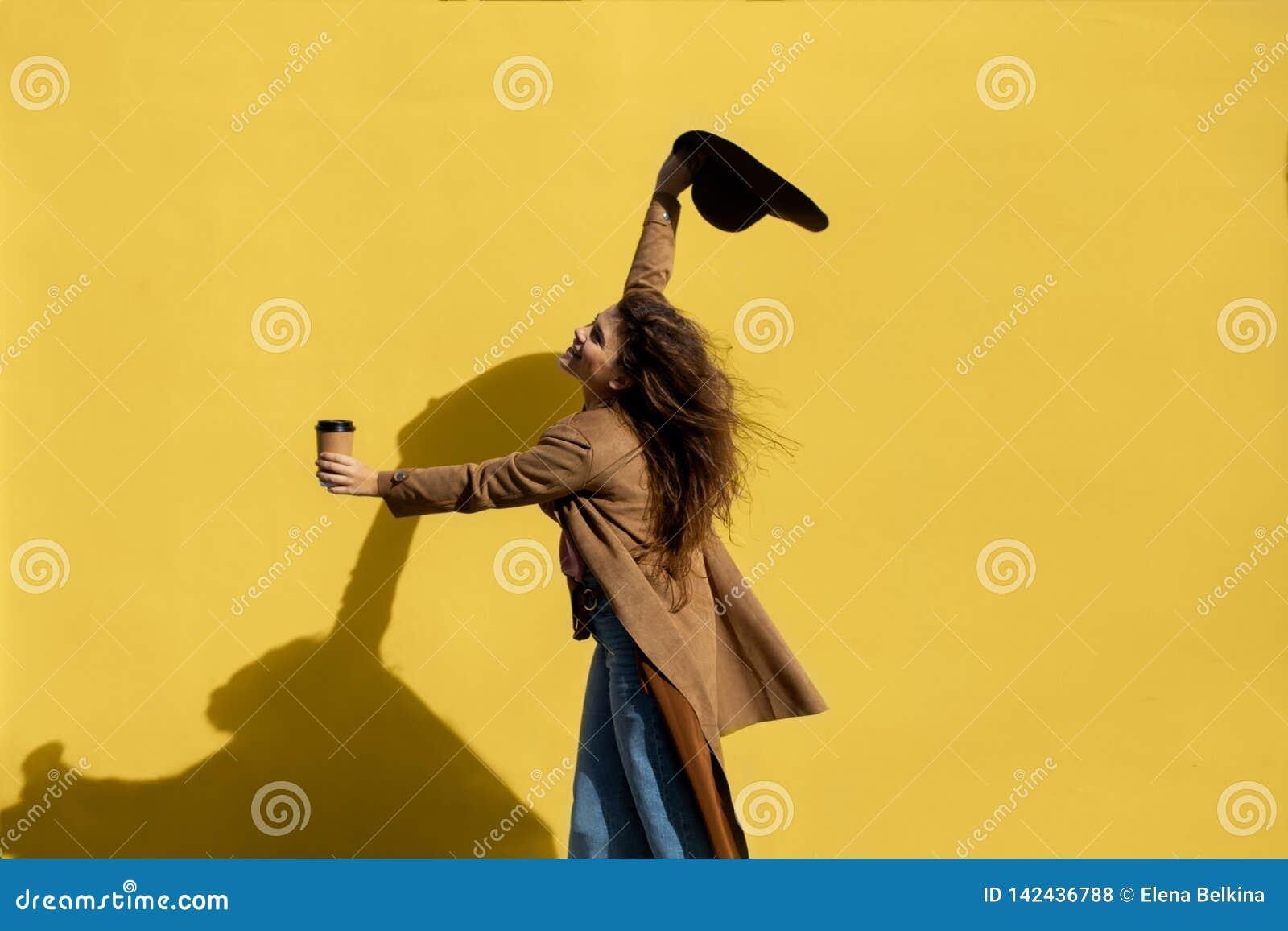 Flicka med en kopp kaffe på en solig dag nära den gula väggen