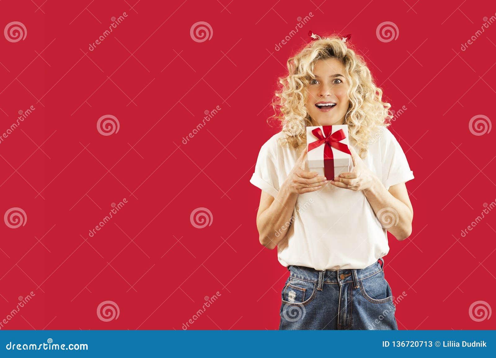 Flicka med en vit gåva i hennes händer på en röd isolerad oavkortad tillväxt för bakgrund Begrepp för vänner dag, valentin dagbeg