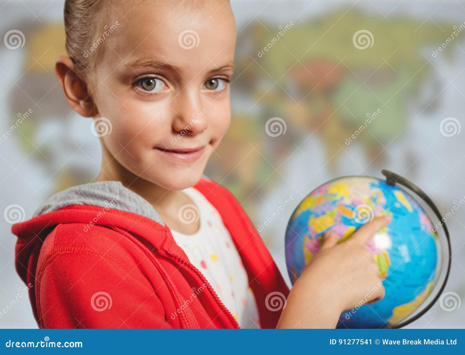 Flicka med jordklotet mot oskarp översikt