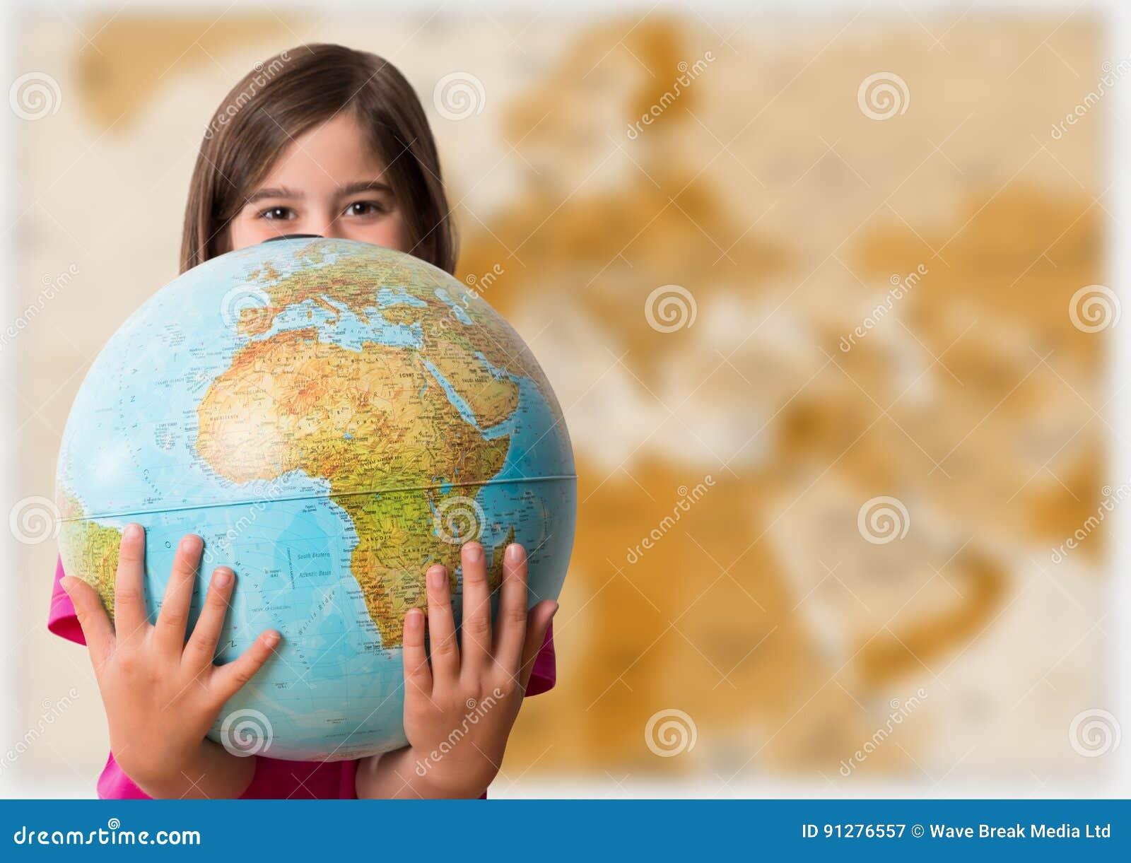Flicka med jordklotet mot oskarp brun översikt
