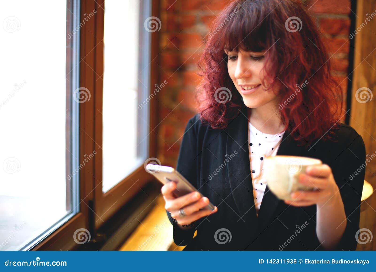 Flicka med kaffe och telefonen