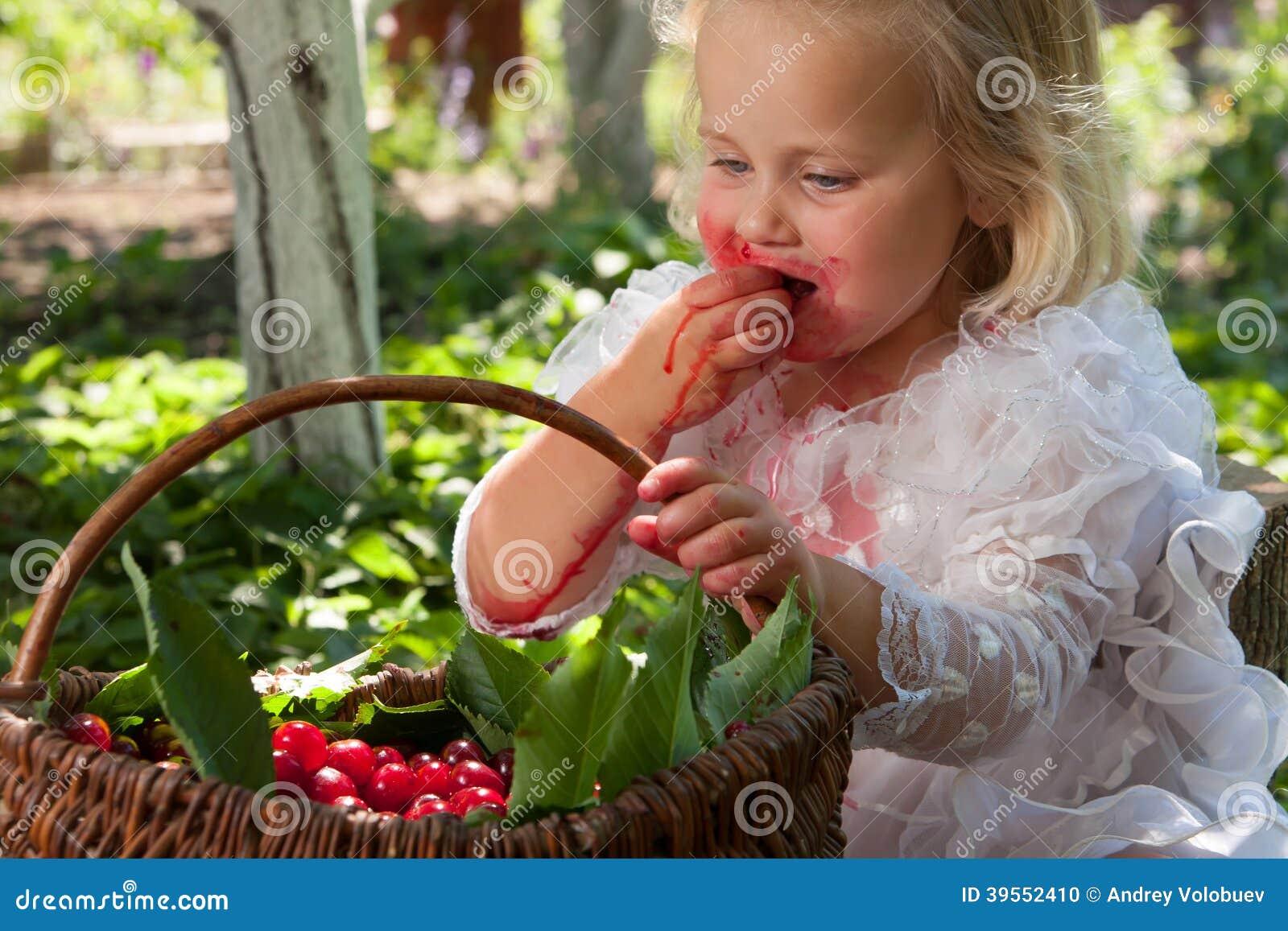 Flicka med korgen av körsbär