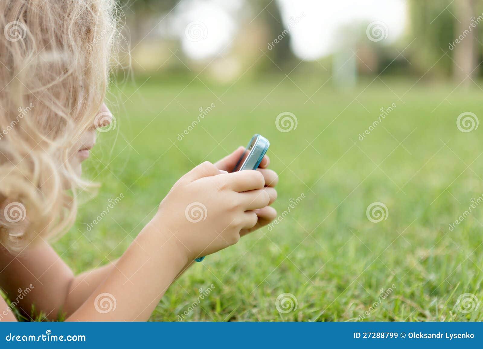 Flicka med mobiler som vilar på gräset