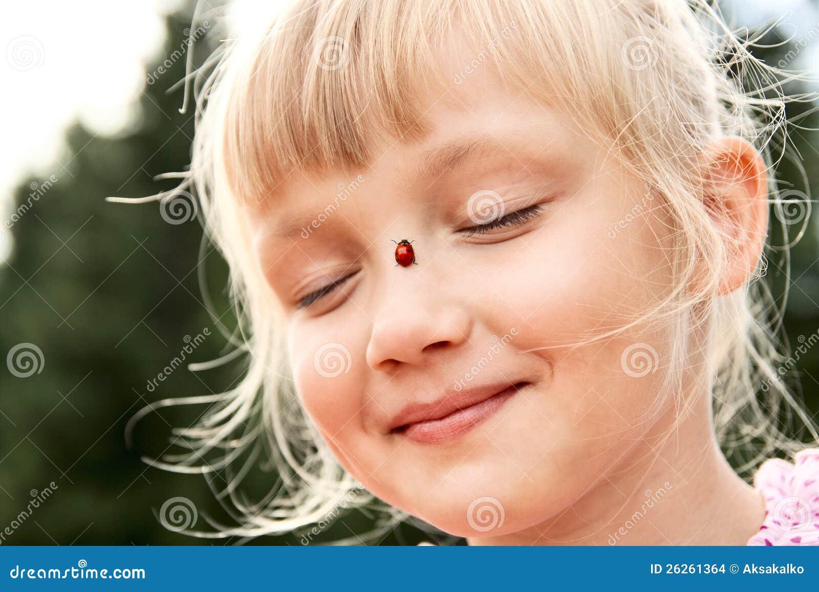 Flicka med nyckelpigan på henne näsa