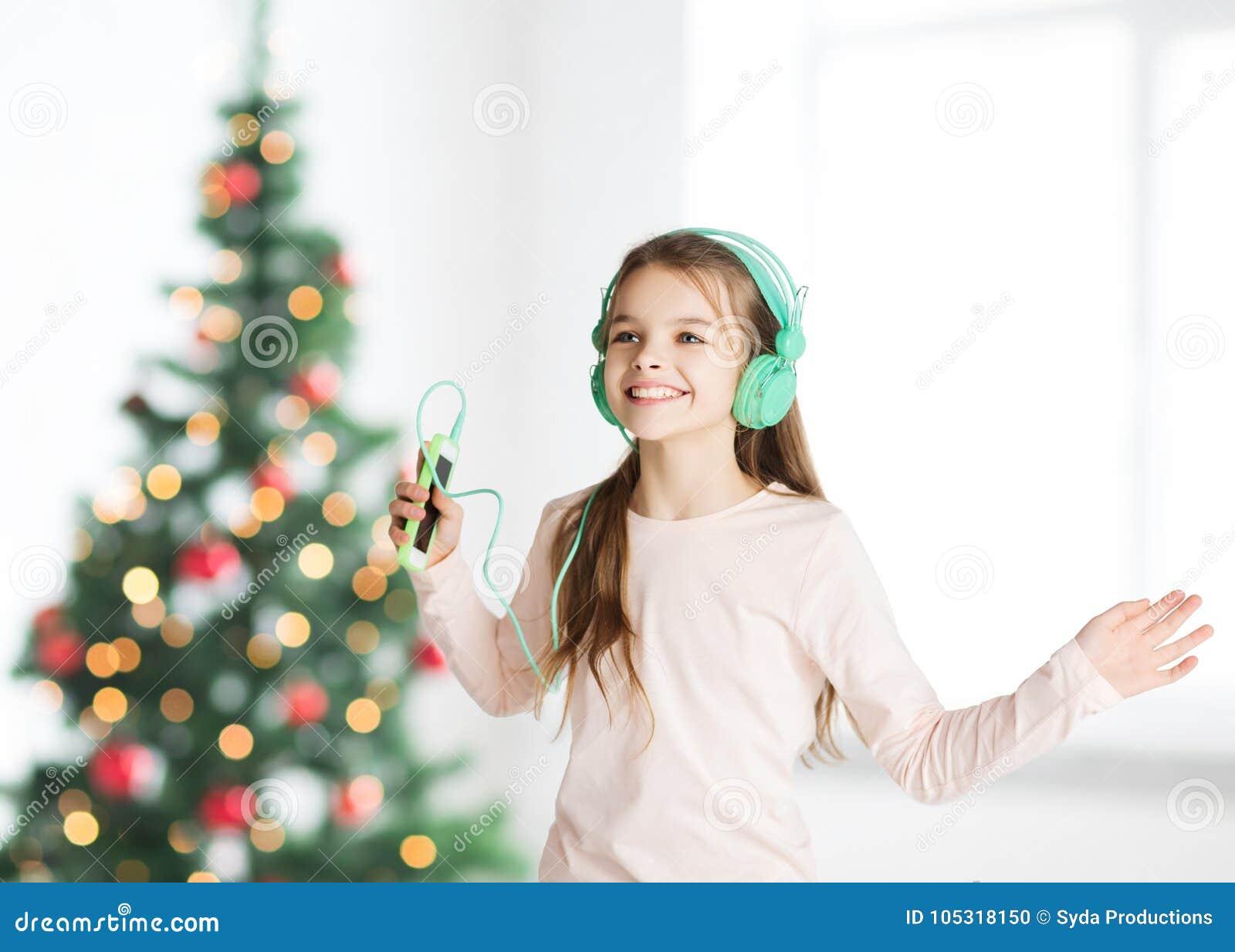 Flicka med smartphonen och hörlurar på jul