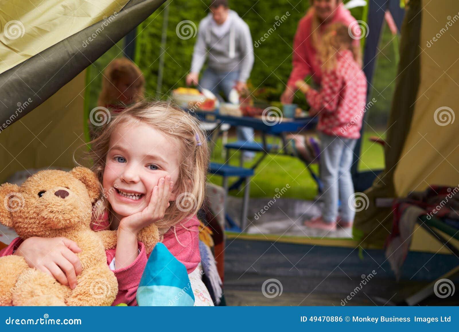 Flicka med Teddy Bear Enjoying Camping Holiday på campingplats