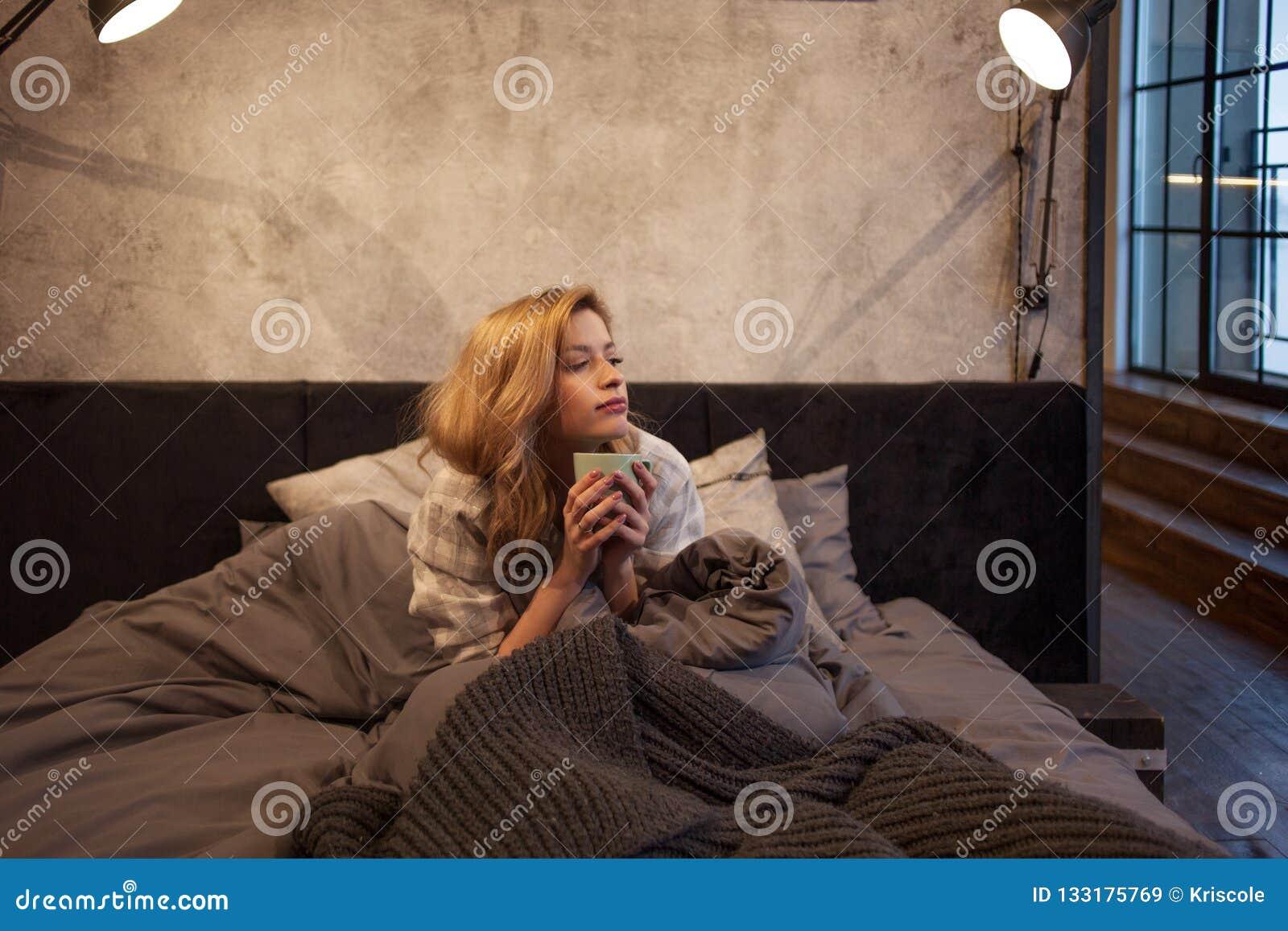 Flicka morgondrinkkaffet i säng Ottan sol hade inte uppstiget ännu