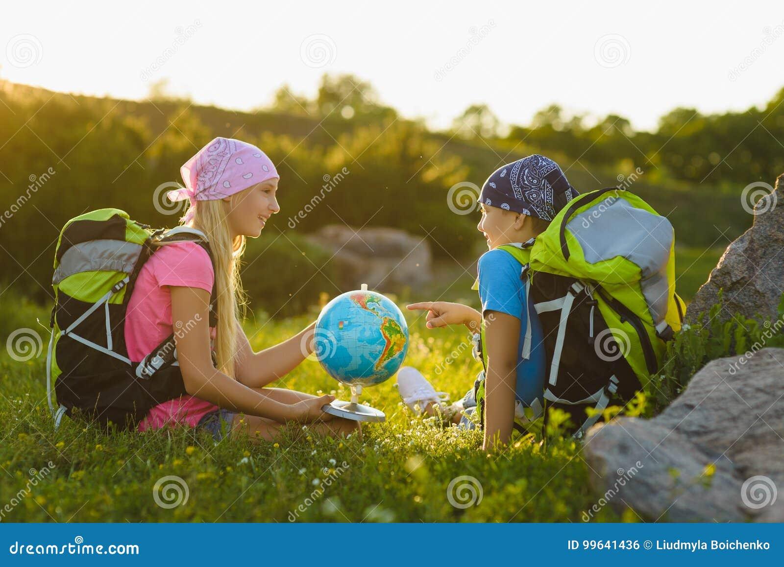 Flicka och pojke med ryggsäckar och att vila för jordklot som är utomhus- Affärsföretag loppbegrepp
