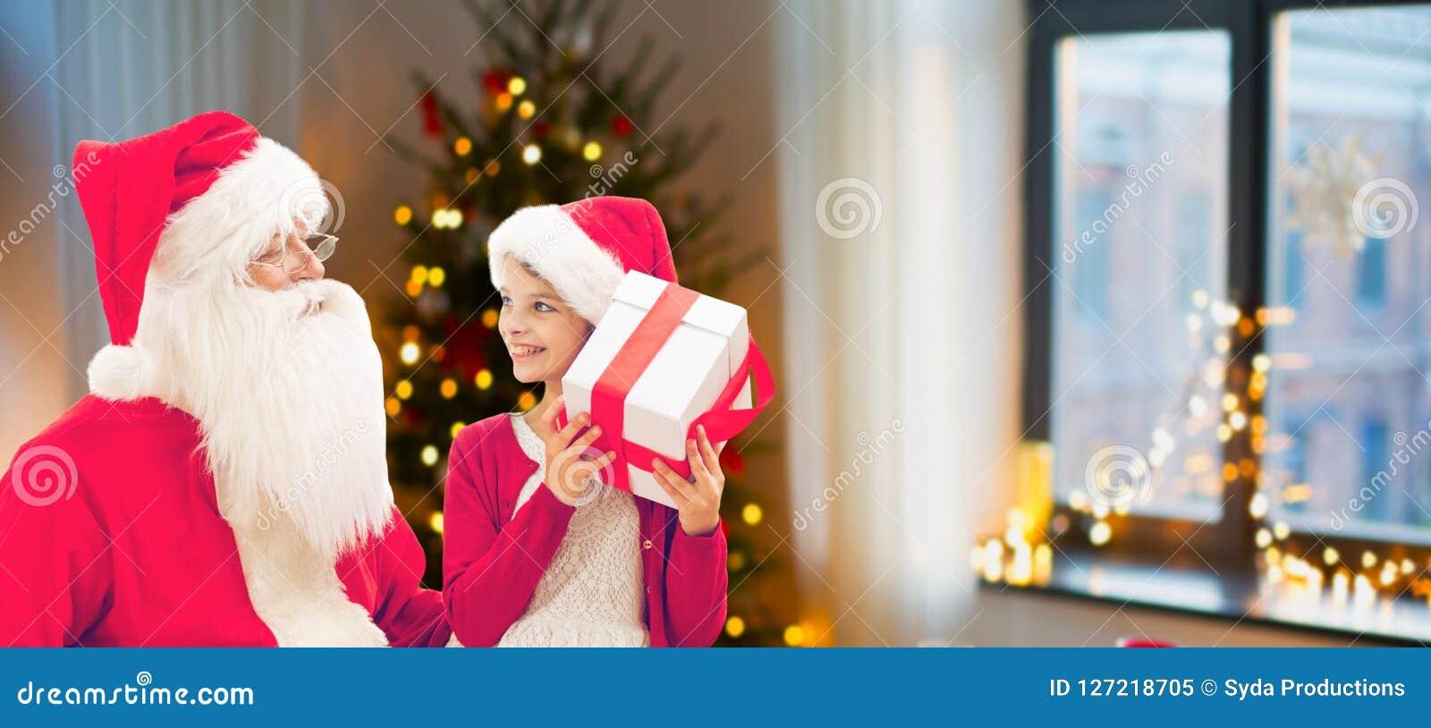 Flicka och santa med julgåvor hemma