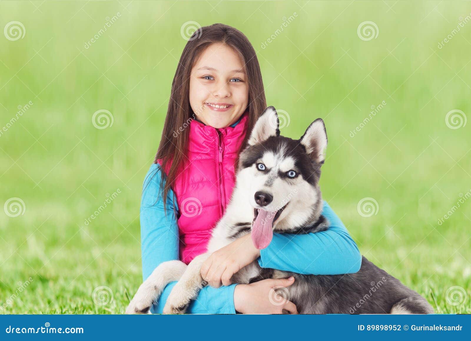 Flicka och Siberian skrovligt på det gröna gräset