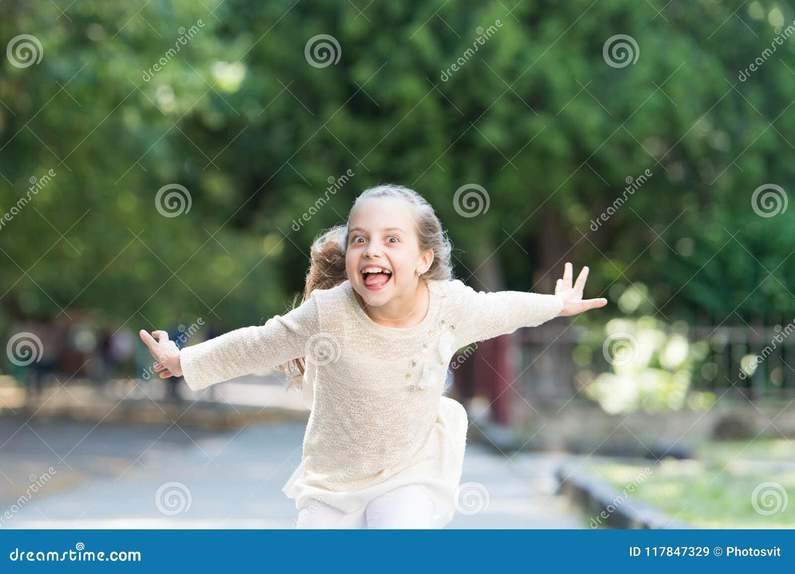 Flicka på den lyckliga le framsidan, natur på bakgrund Det gladlynt barnet som är lyckligt och, tycker om går parkerar in letters