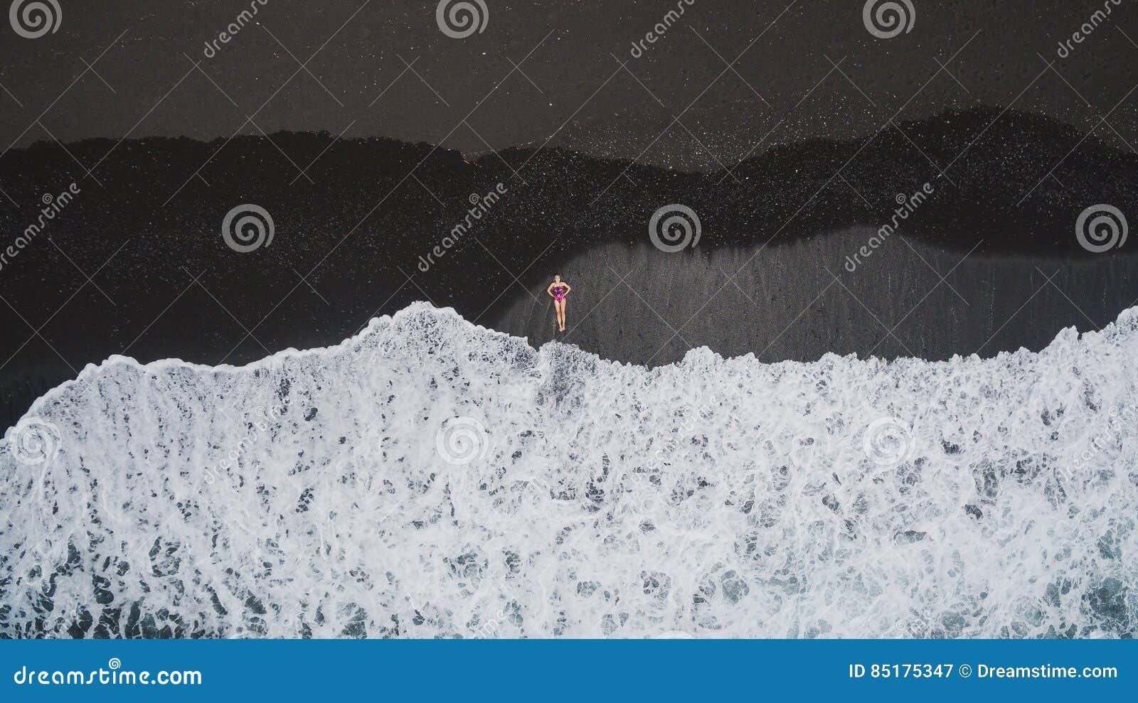 Flicka på den svarta sandstranden