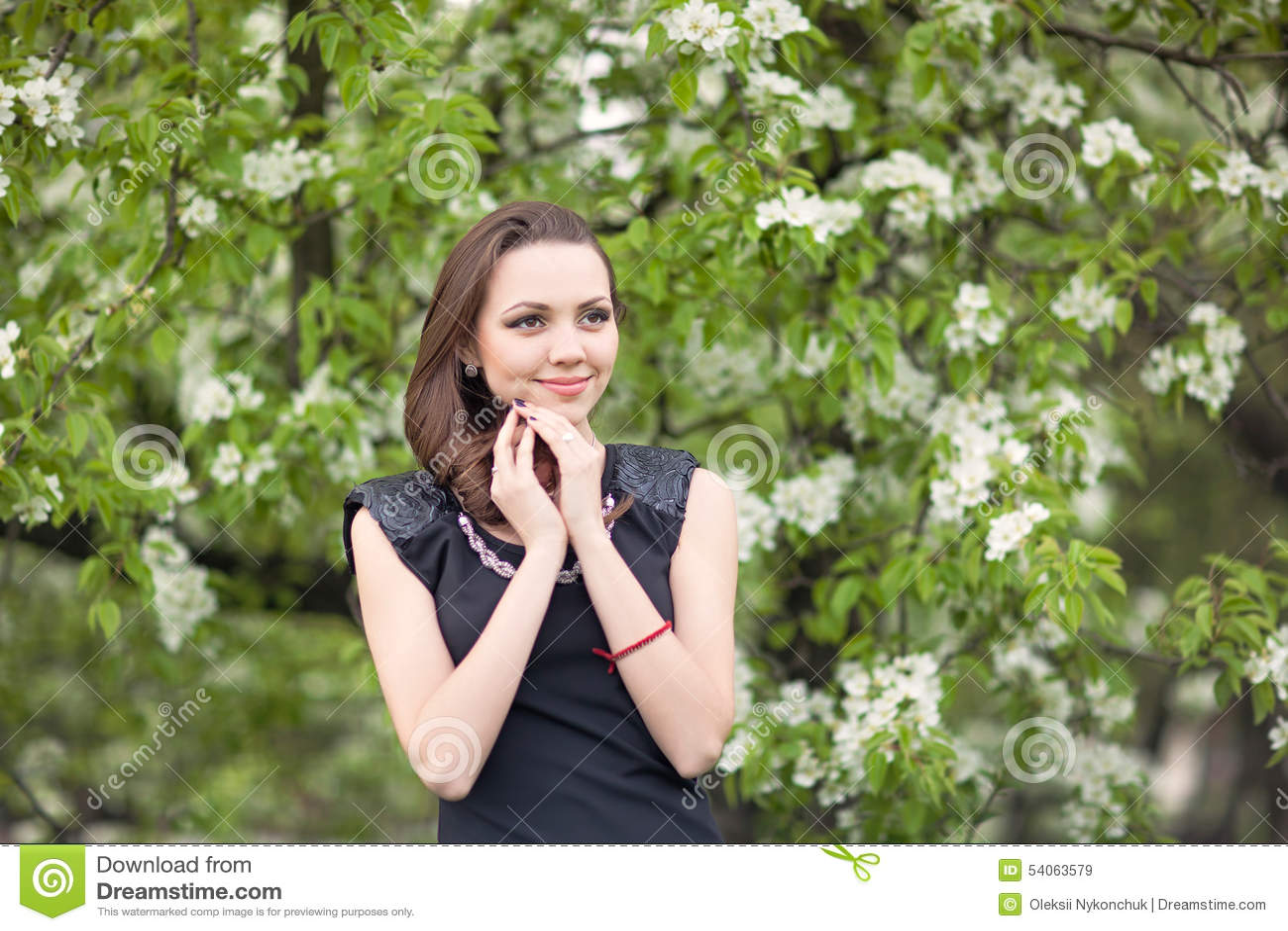 Flicka på en bakgrund av ett blomstra träd