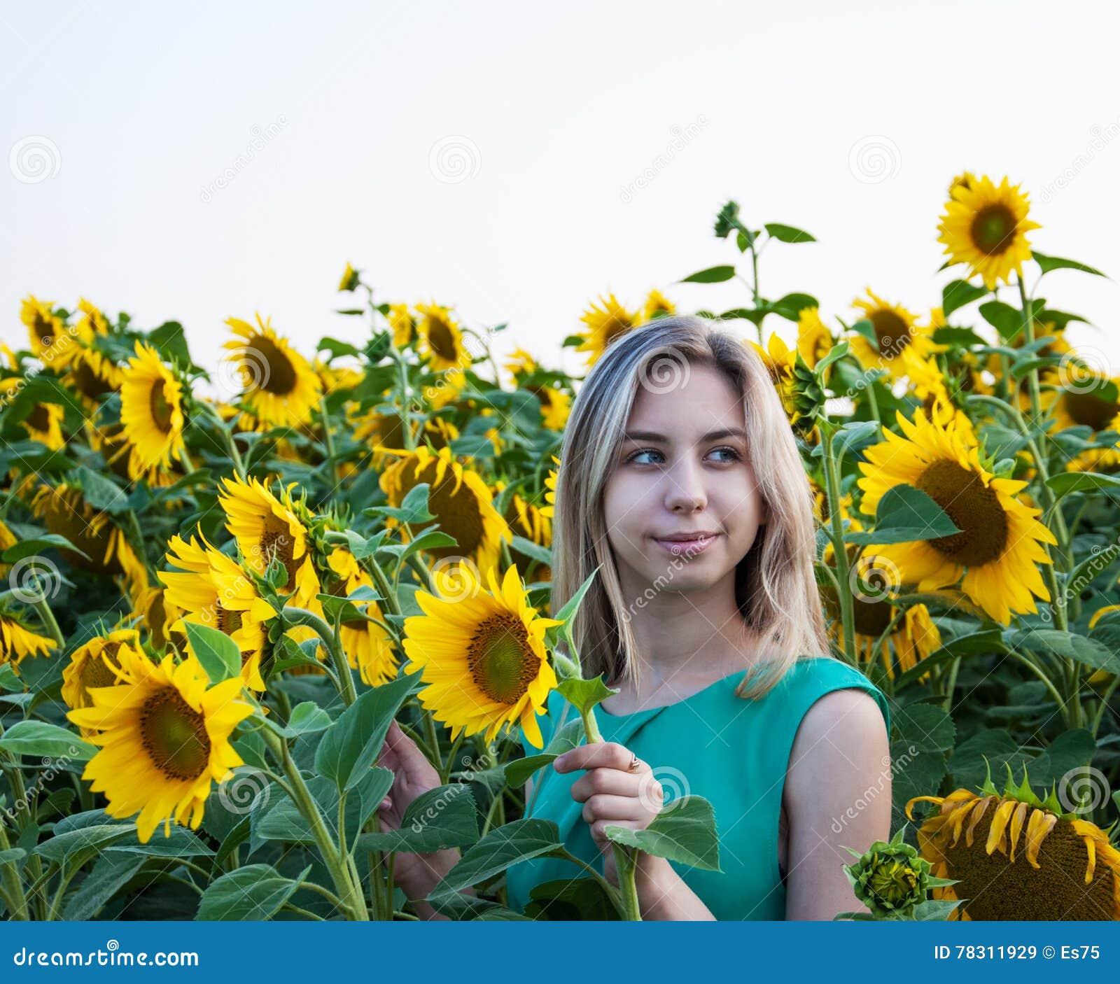 Flicka på fältet av solrosor