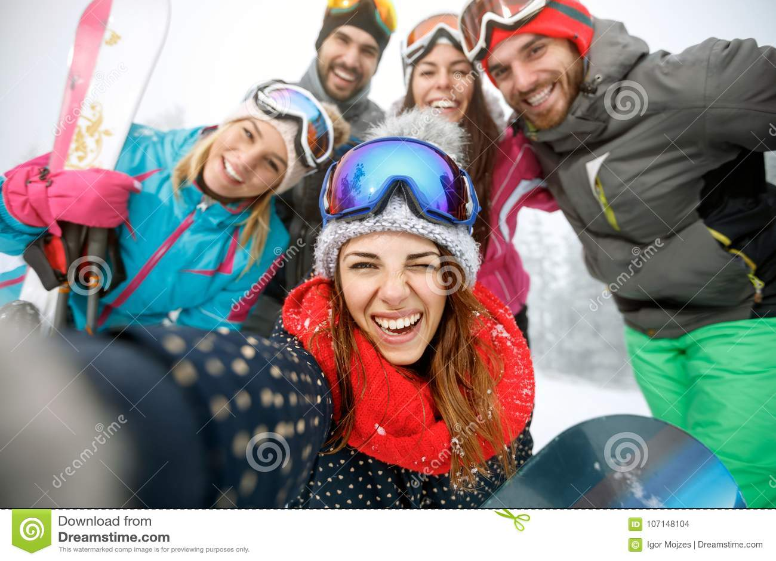 Flicka på skidåkning med gruppen av vänner
