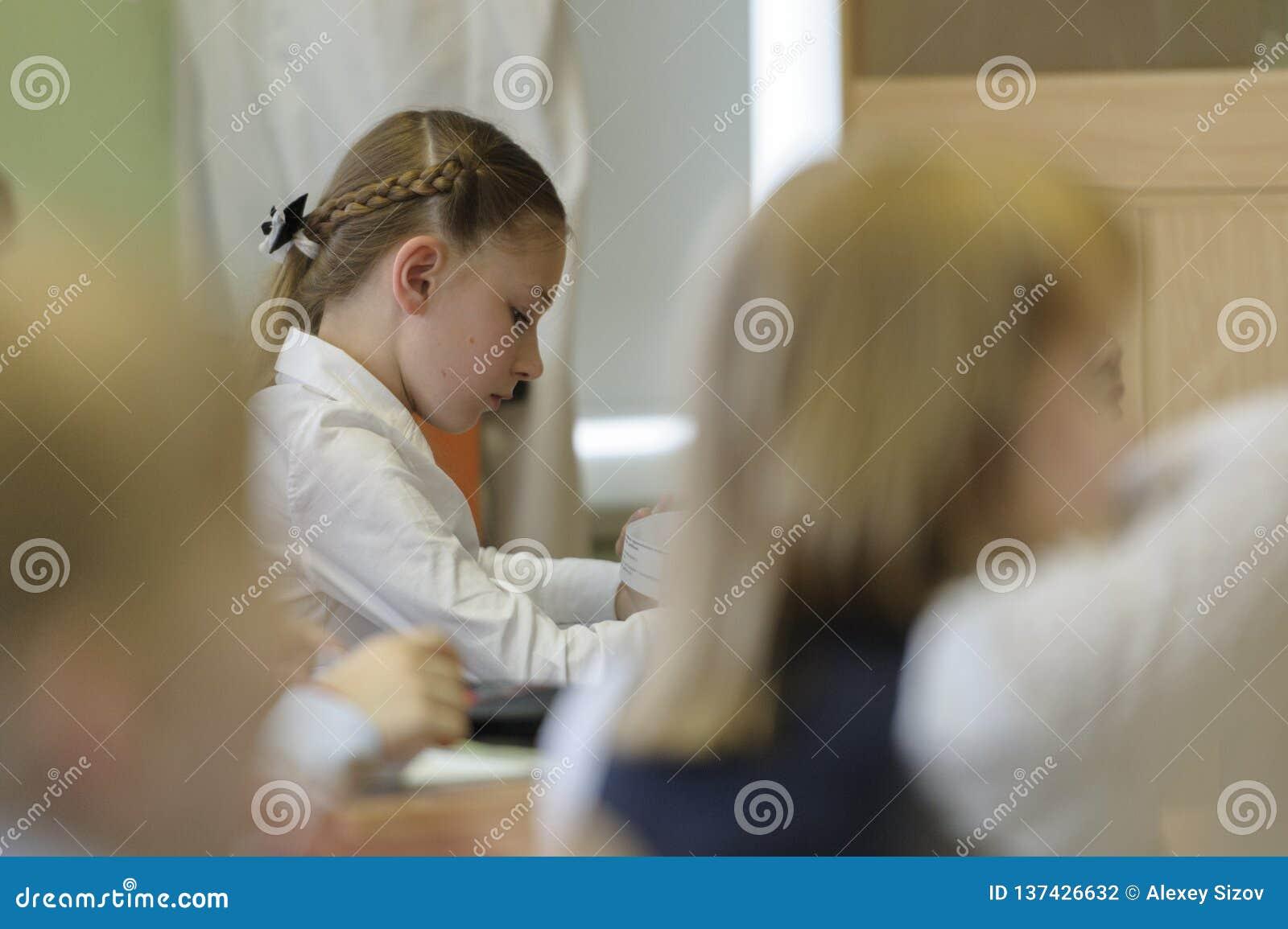 Flicka på skola som lyssnar till läraren