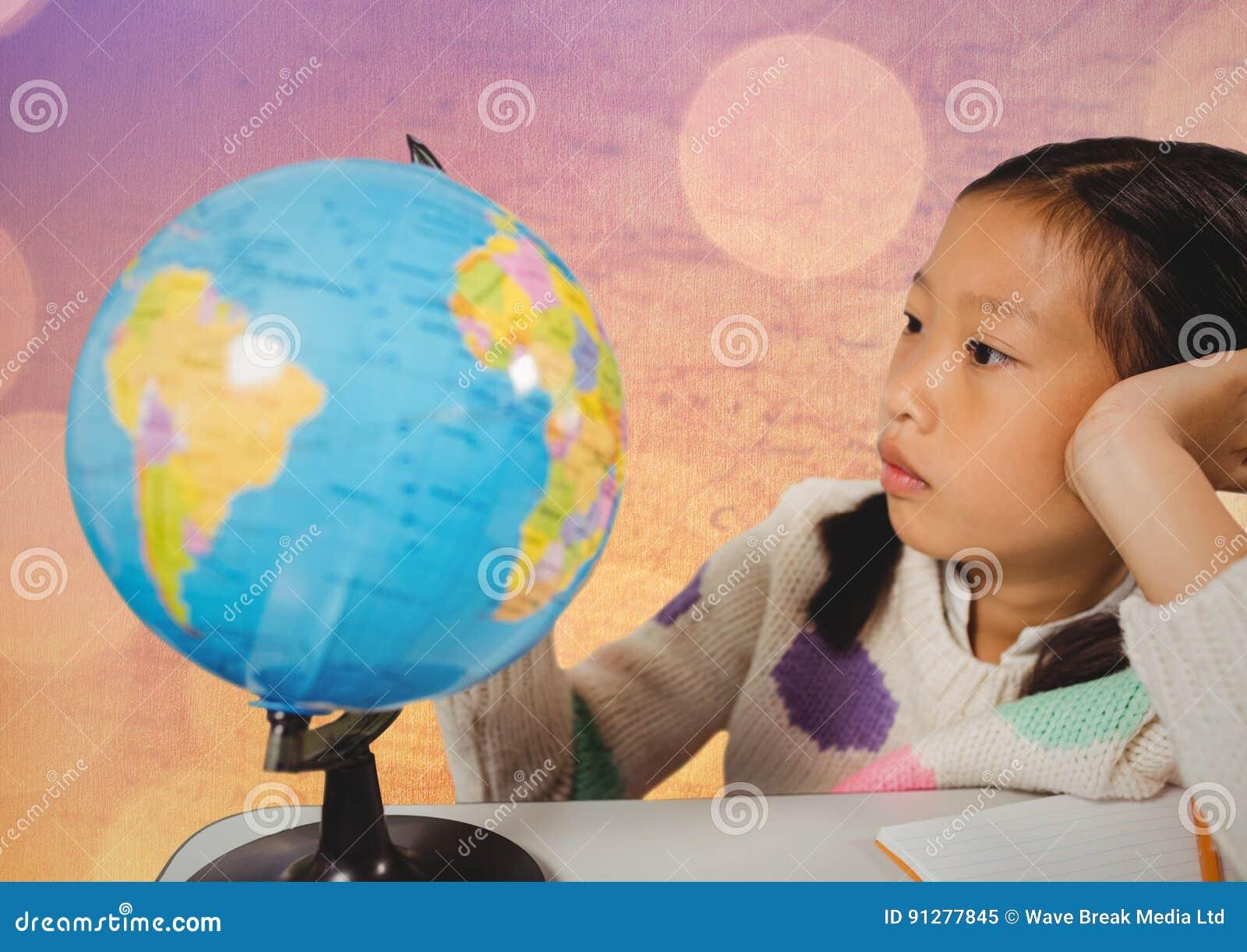Flicka på skrivbordet med jordklotet mot översikt med bokeh