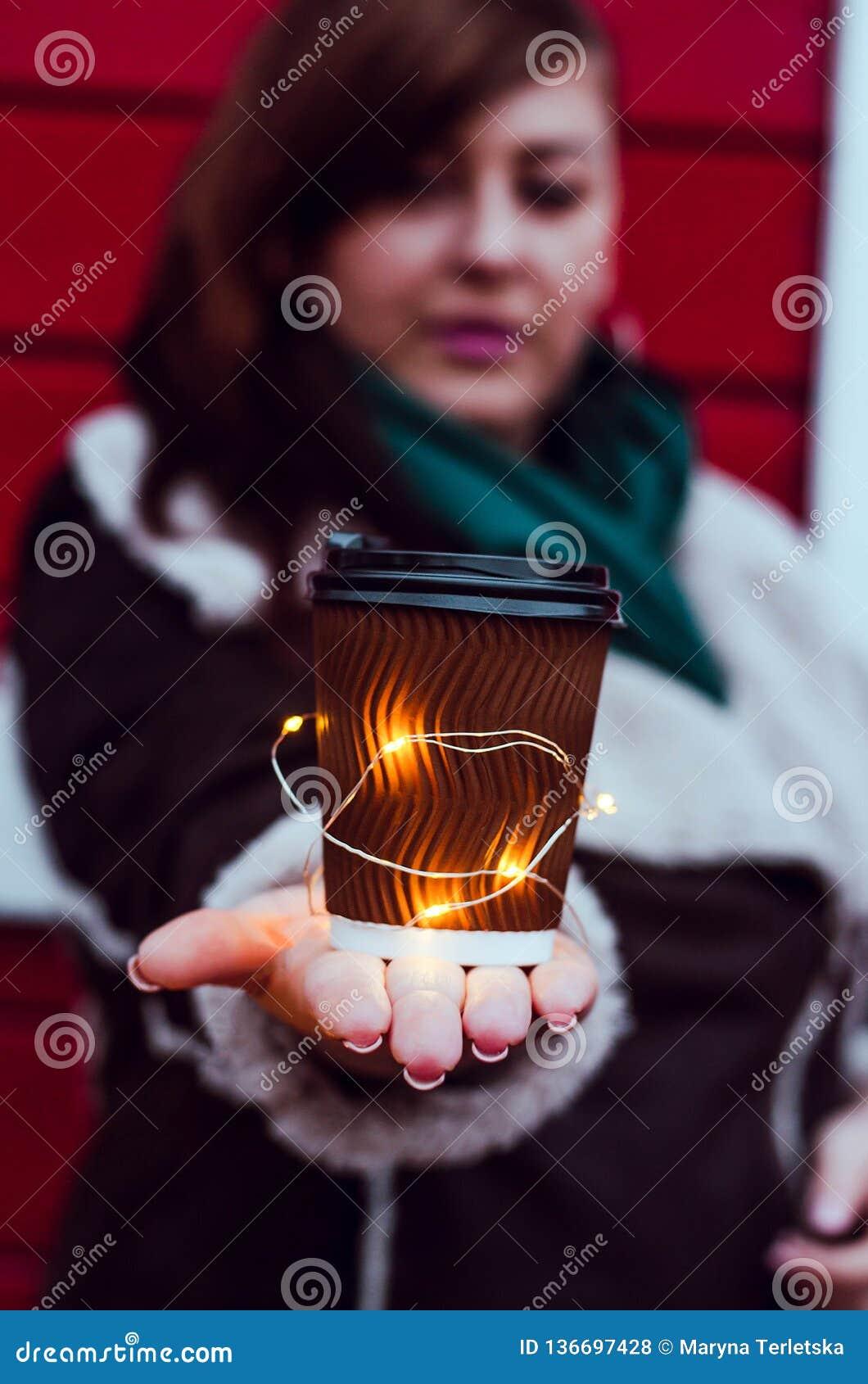 Flicka plus format med ett exponeringsglas av kaffe och en ljus girland