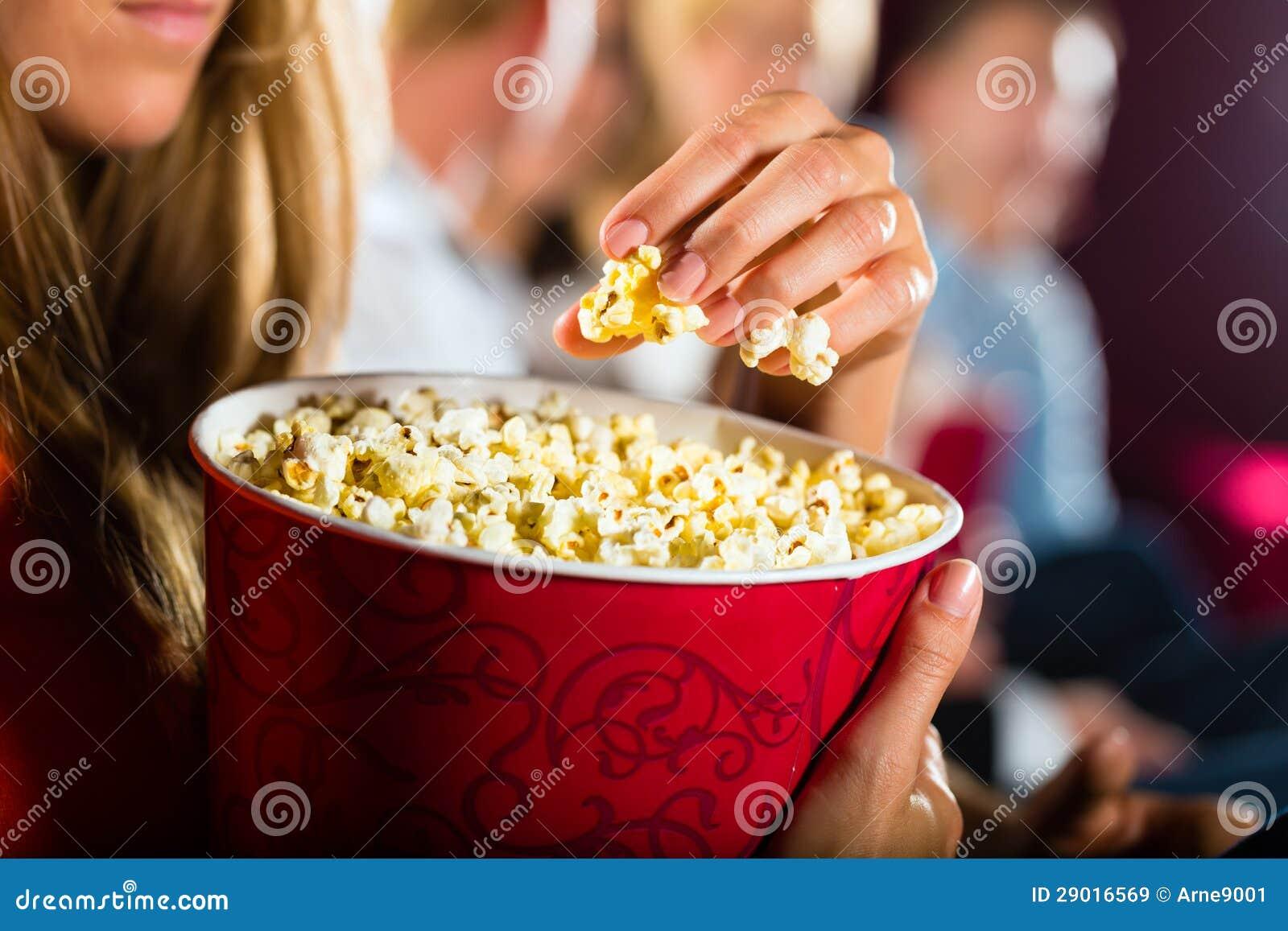 Flicka som äter popcorn i bio eller filmbiograf