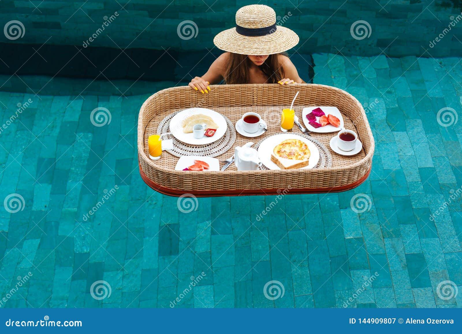 Flicka som äter sväva frukosten i pöl för lyxigt hotell