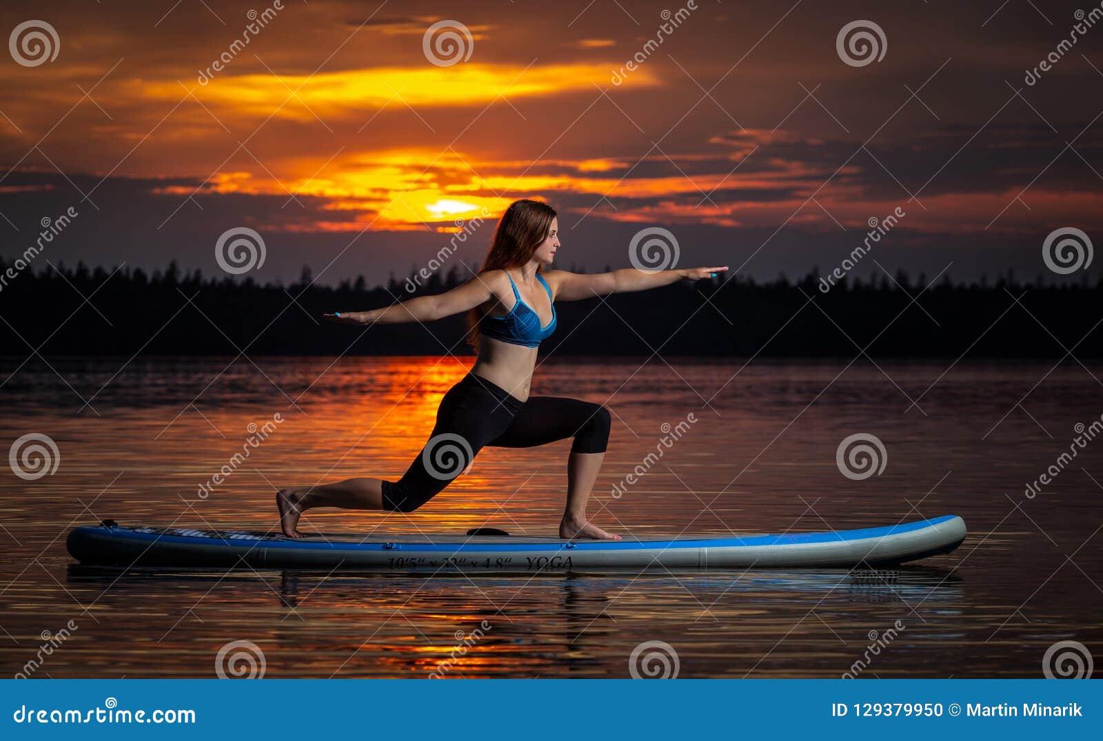 Flicka som övar yoga på paddleboard i solnedgången på den sceniska sjön Velke Darko