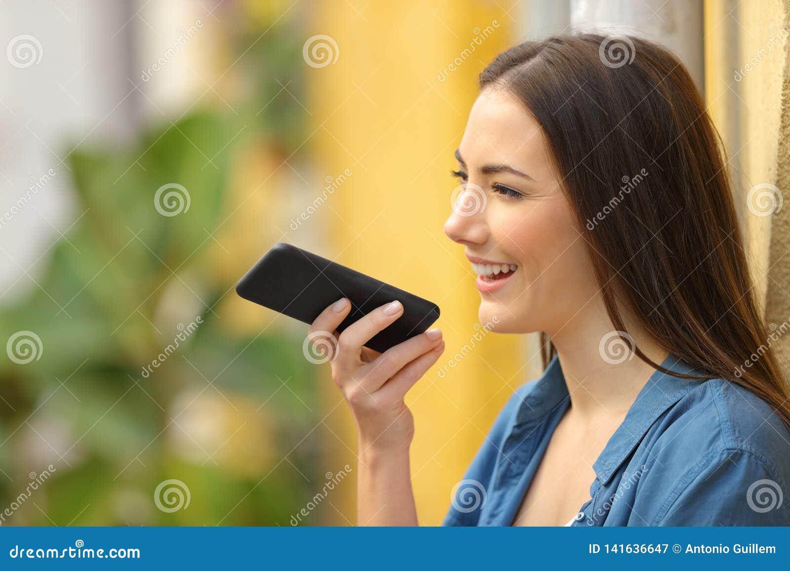 Flicka som använder stämmaerkännande på telefonen i en färgrik gata