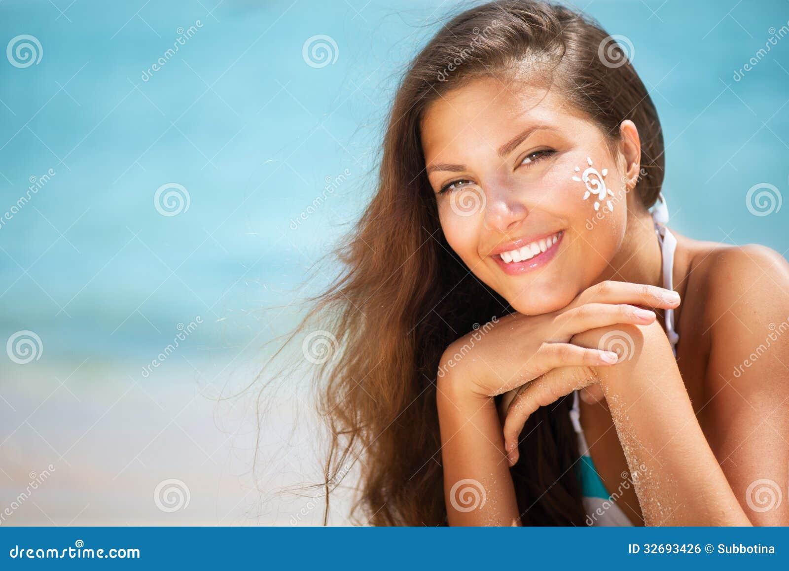 Flicka som applicerar Sun Tan Cream