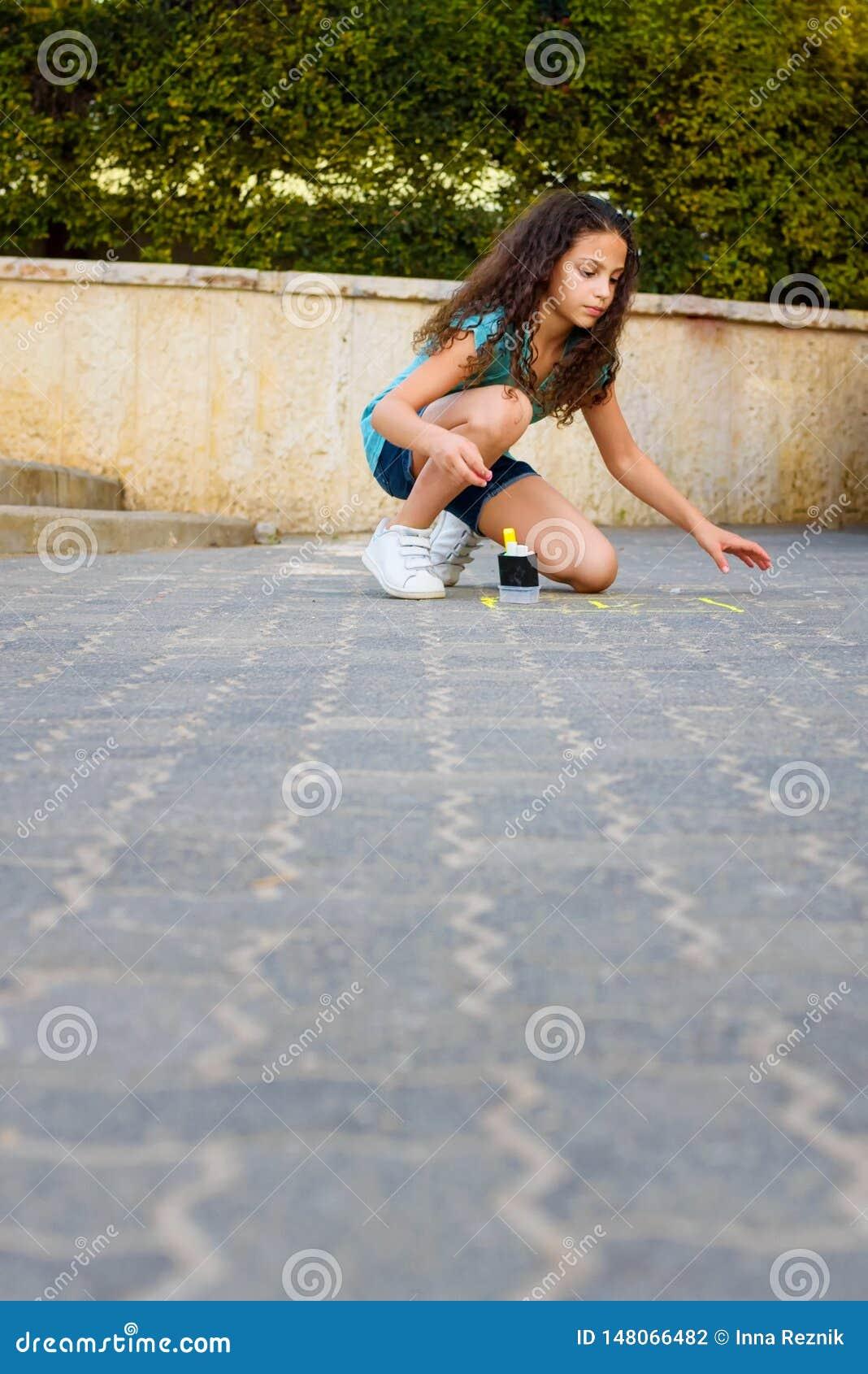 Flicka som drar hoppa hage med krita p? lekplats