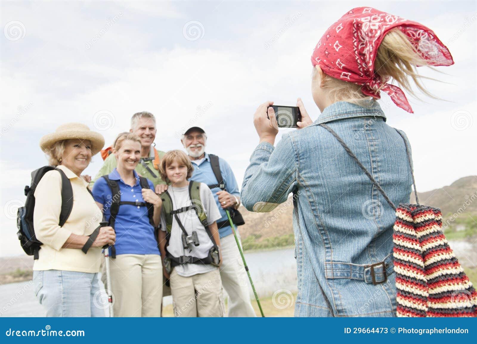 Flicka som fotograferar familjståenden