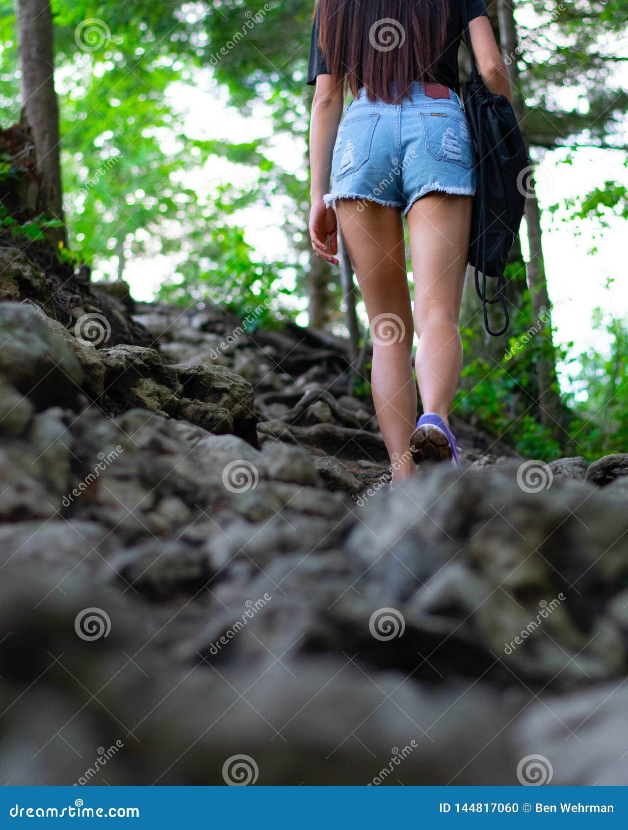 Flicka som fotvandrar i skogen
