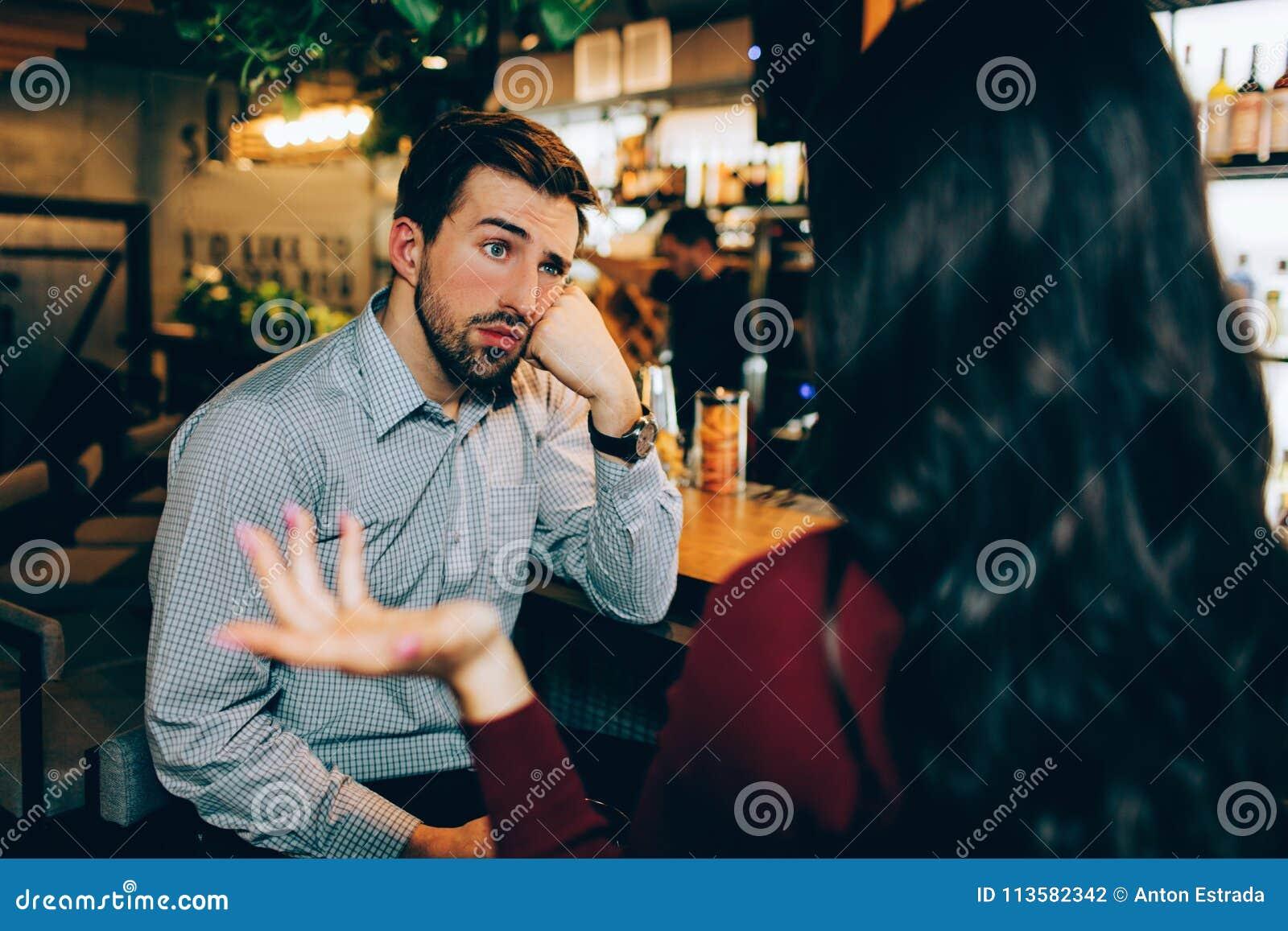 Flicka som framme sitter av ung grabb och talar till honom Han ser uttråkad Mannen är inte intresserad i konversation alls